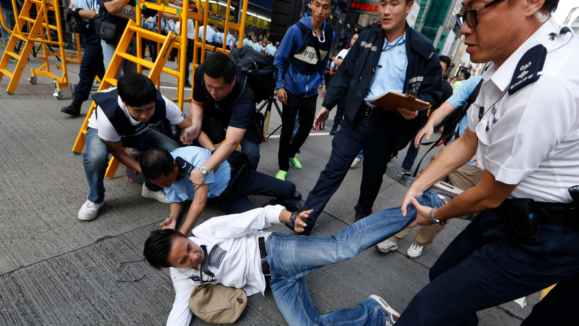 Nov. 25, 2014: A man is taken away by police officers as workers start clearing away barricades at an occupied area in Mong Kok district of Hong Kong