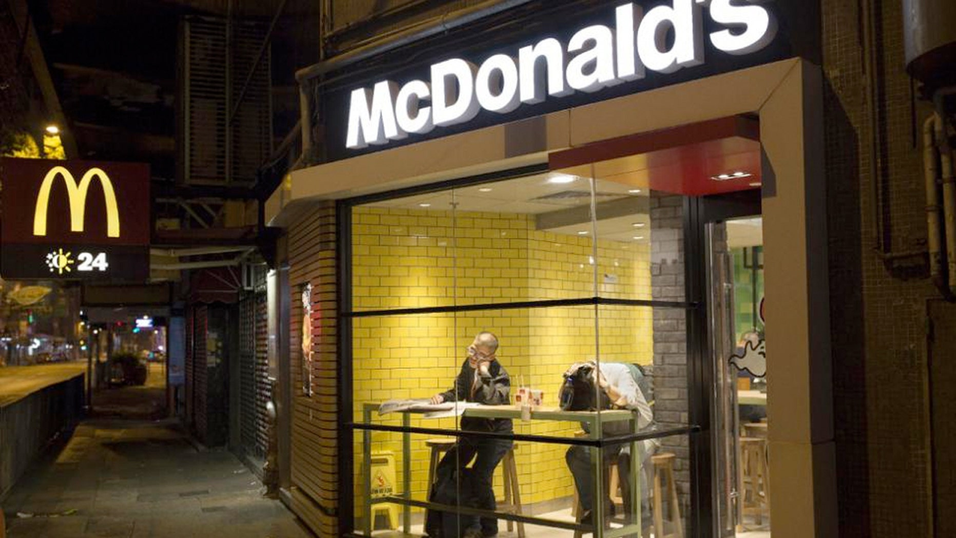 Two men sleep with their belongings at night in a 24-hour McDonald's branch in Hong Kong.