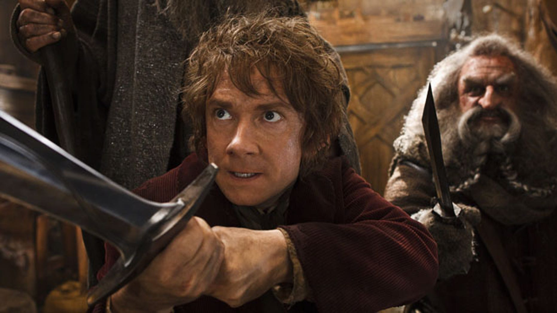 """This image released by Warner Bros. Pictures shows Martin Freeman, left, and John Callen in a scene from """"The Hobbit: The Desolation of Smaug.""""  The Hobbit: The Desolation of Smaug held off Anchorman 2 on a busy weekend at the box office. According to studio estimates Sunday, Peter Jacksons Hobbit sequel took in $31.5 million in its second weekend of release. That topped Will Ferrells Anchorman sequel, which nevertheless opened strongly in second place."""