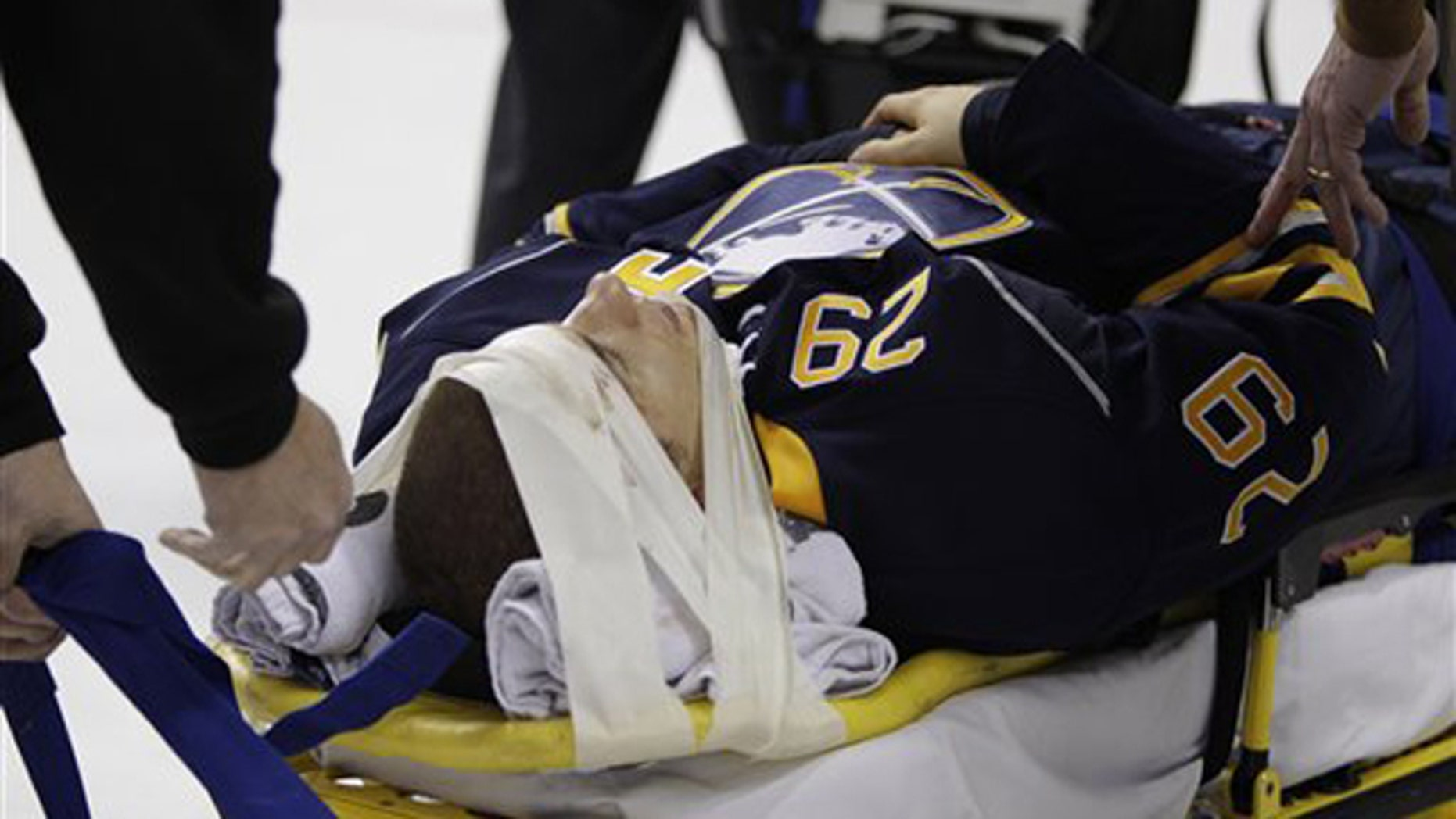 In this Oct. 11, 2010, file photo Buffalo Sabres' Jason Pominville is carted off the ice after a hit which resulted in a gash above his eye and a concussion during an NHL hockey game against the Chicago Blackhawks in Buffalo, N.Y.