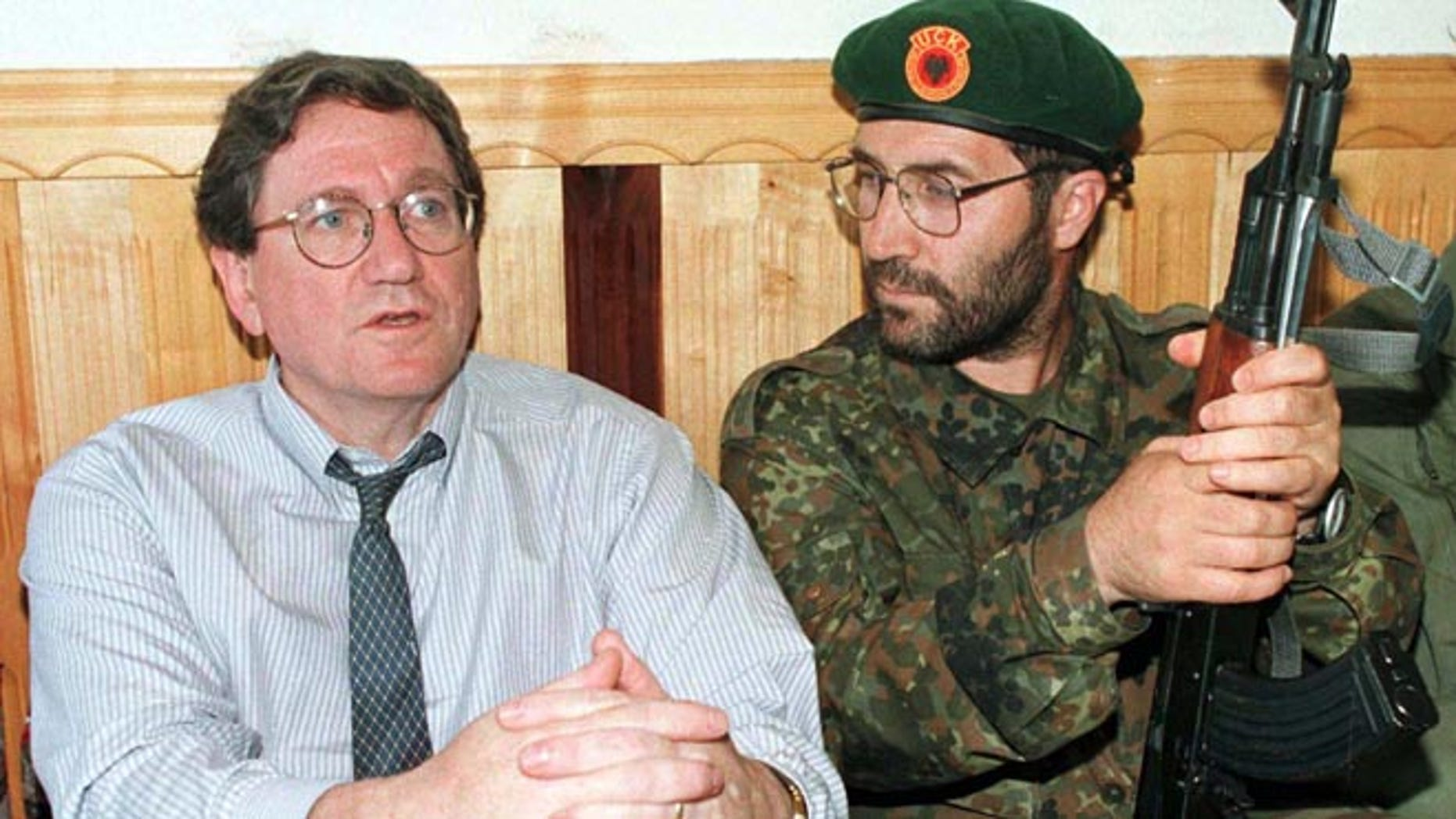 FILE 1998: Special U.S. envoy for the Balkans Richard Holbrooke, left, sits with an unidentified Kosovo Liberation Army soldier at their headquarters in Junik.