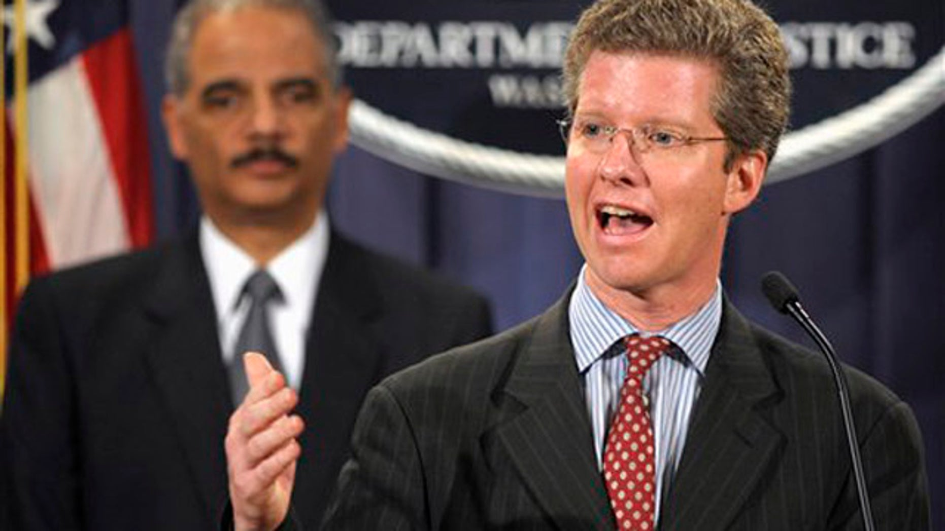 Jan. 27, 2012: Attorney General Eric Holder, left, watches as Housing and Urban Development Secretary Shaun Donovan speaks at the Justice Department in Washington.