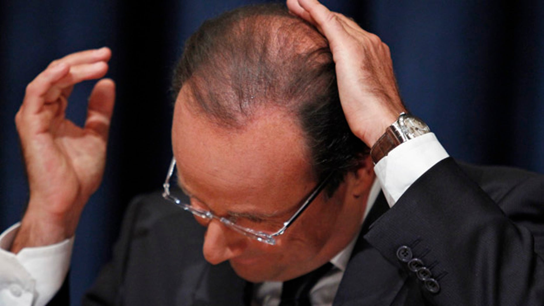FILE: France's President Francois Hollande smoothes down his hair during a news conference in New York.