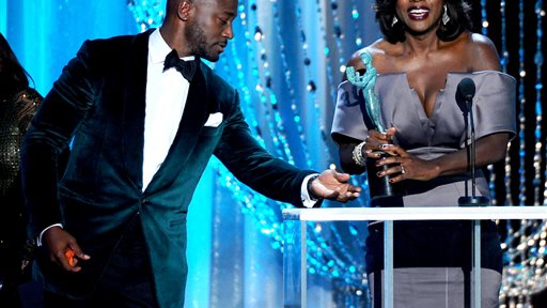 """FILE - In this Saturday, Jan. 30, 2016 file photo, Taye Diggs, left, presents Viola Davis with the award for outstanding female actor in a drama series for """"How to Get Away with Murder"""" at the 22nd annual Screen Actors Guild Awards at the Shrine Auditorium & Expo Hall in Los Angeles.  A coalition of advocacy groups is calling on major Hollywood film studios to broaden their diversity efforts to include Hispanics, Asian-Americans and Indians as well as blacks. (Photo by Vince Bucci/Invision/AP, File)"""