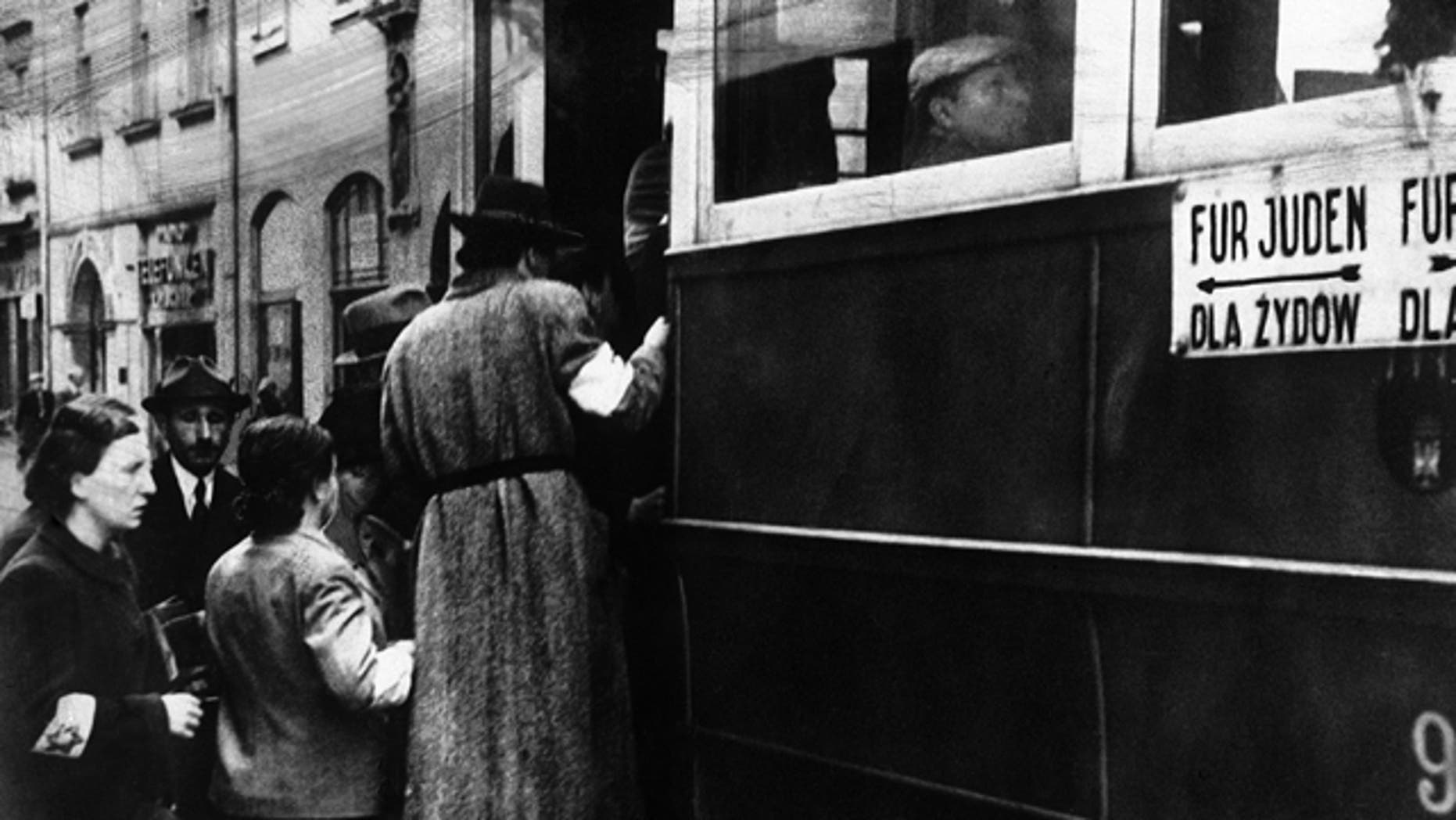 Feb. 17, 1941: FILE - This file photo shows a scene in the Warsaw Ghetto where Jews wearing white armlets bearing the Star of David board a tram marked with the words For Jews Only.