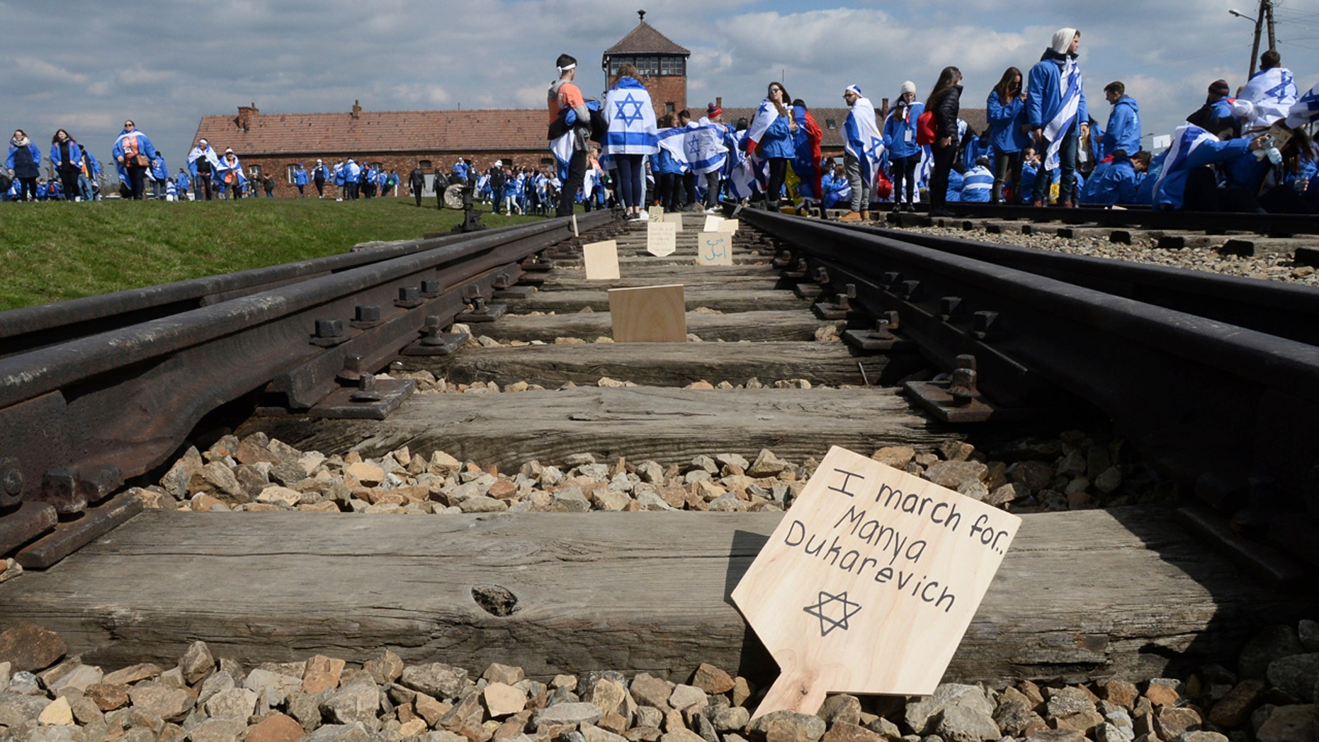 Participants of the yearly March of the Living place memory plaques on the rails in the former German Nazi Death Camp Auschwitz-Birkenau, in Brzezinka, Poland, Monday, April 24, 2017.