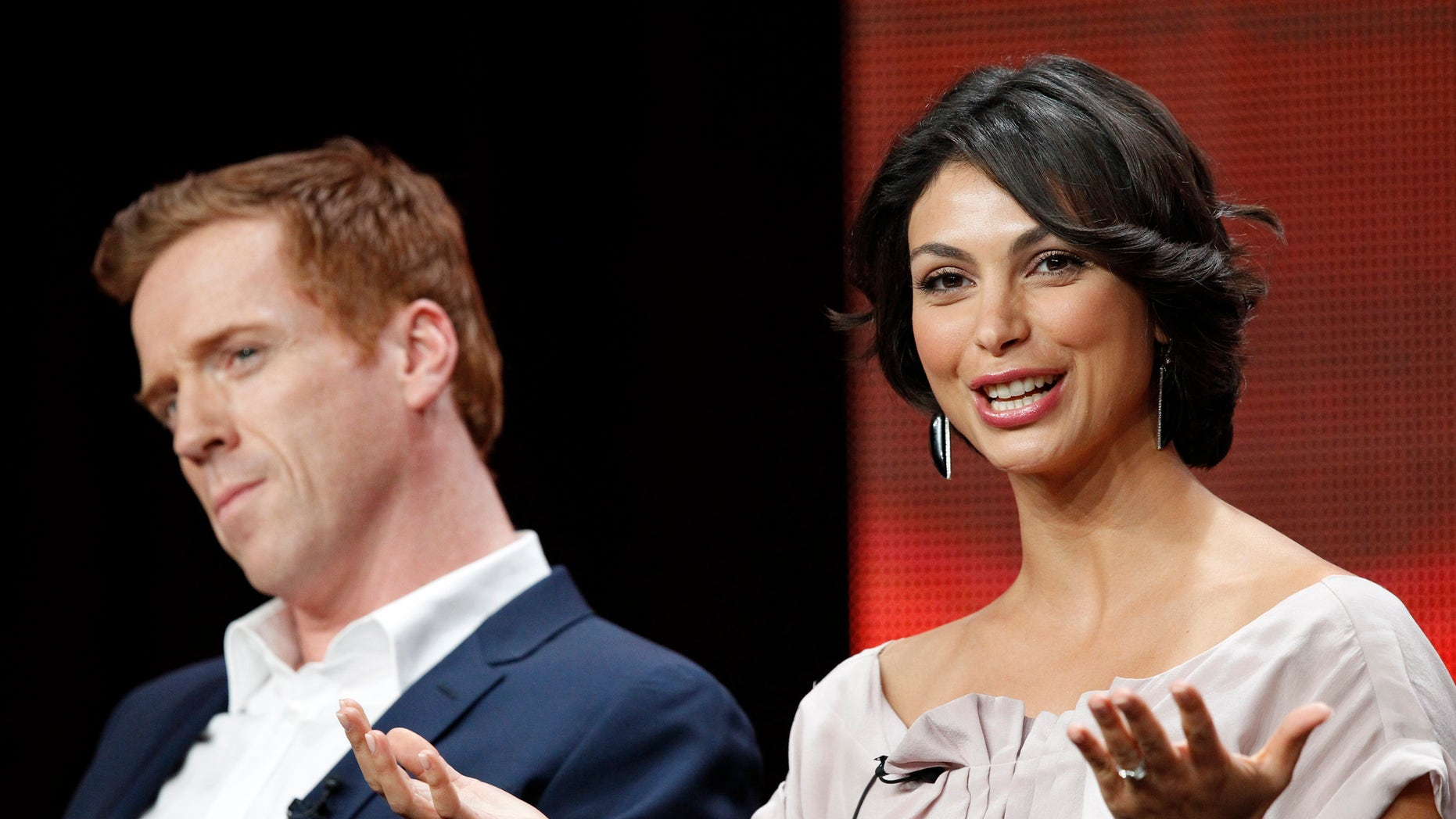 """July 30, 2012. Cast member Morena Baccarin speaks, as co-star Damian Lewis watches, at a panel for """"Homeland"""" during the Showtime television portion of the Television Critics Association Summer press tour in Beverly Hills, California."""