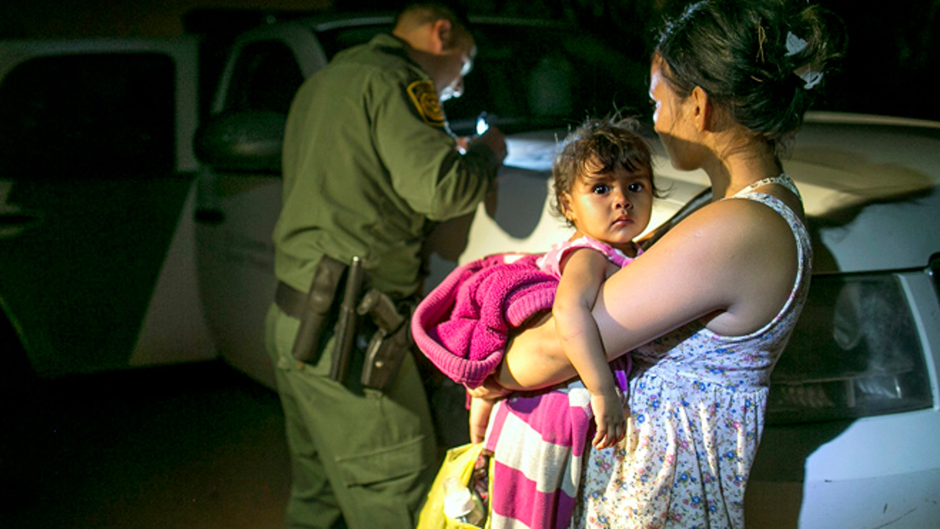 July 3, 2014: Flor Garcia, 19, of Honduras, holds her 1-year-old daughter, Flor Fernandez, after they turned themselves over to Customs and Border Protection Services agents after crossing the Rio Grande from Mexico near McAllen, Texas.