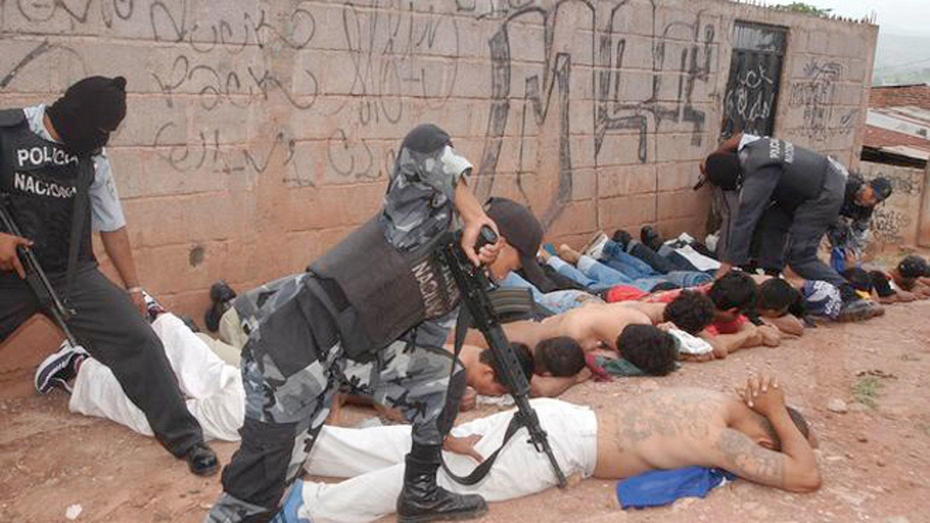 Police officers detain members of the Mara 18 and MS 13 gangs in Honduras.