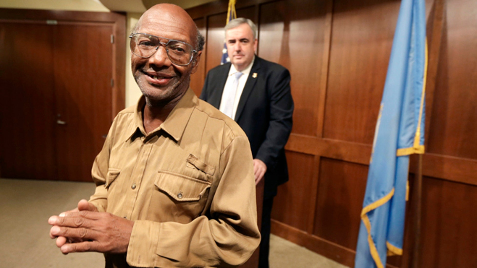 Sept. 16, 2013: Glen James, of Boston, left, smiles in the direction of members of the media as Boston Police Commissioner Edward Davis, right, looks on during a news conference at the police headquarters, in Boston.