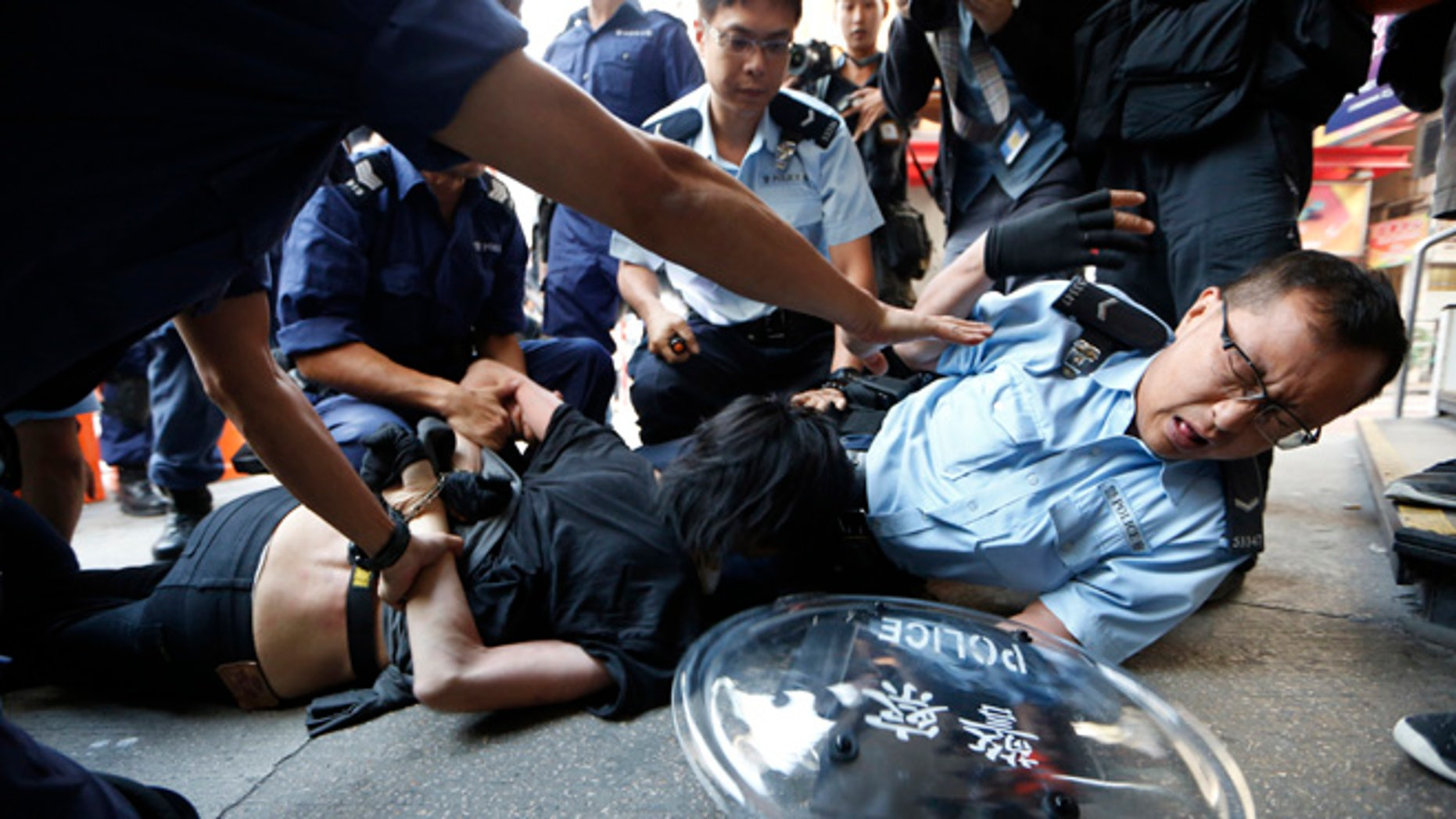 Oct. 17, 2014: A pro-democracy protester is arrested by riot police after police moved in the occupied area by the protesters in the Mong Kok district of Hong Kong. Riot police moved in on a Hong Kong pro-democracy protest zone in a dawn raid on Friday, taking down barricades, tents and canopies that have blocked key streets for more than two weeks.