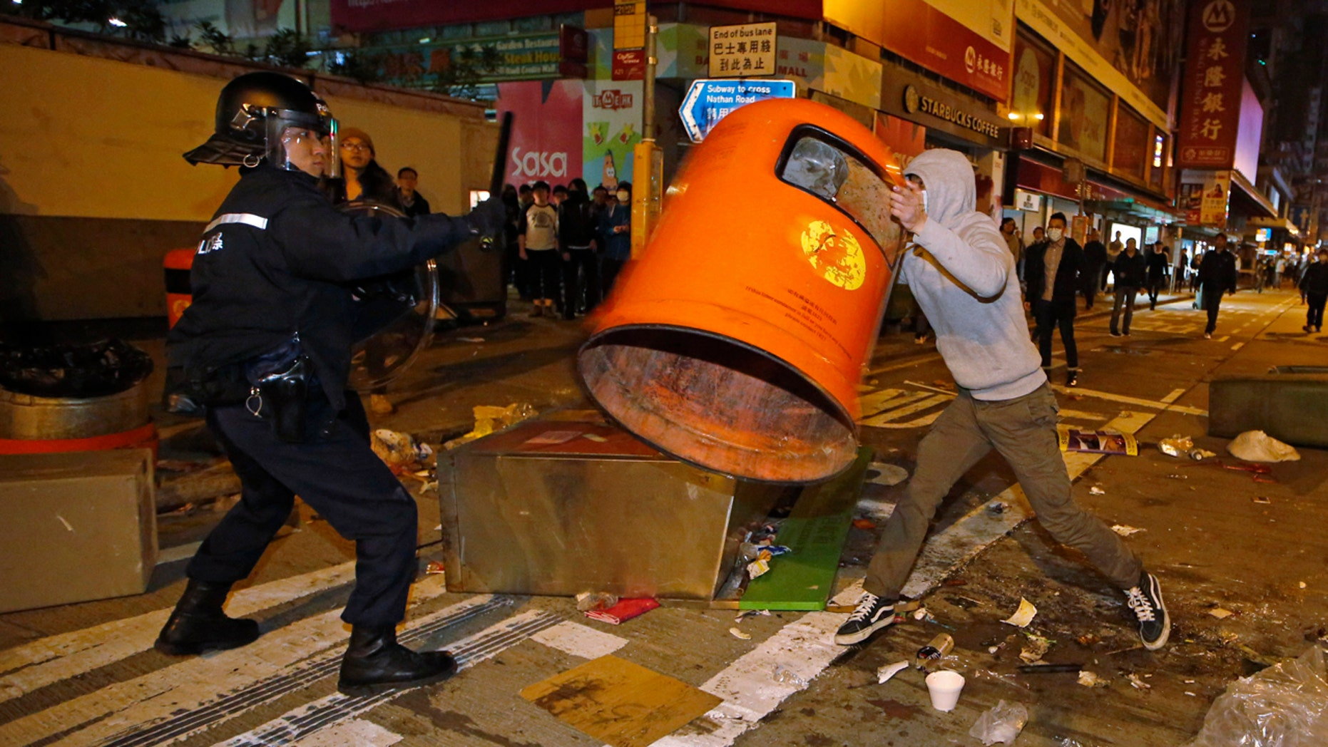 Feb. 9, 2016: A rioter tries to throw a litter bin at police on a street in Mong Kok district of Hong Kong. (AP Photo/Kin Cheung)