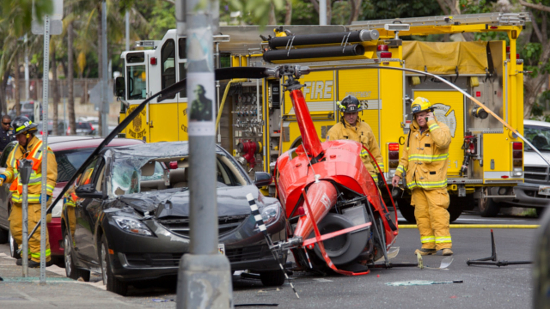 May 8, 2013: Honolulu firefighters look over the wreckage of a small helicopter that crashed next to a car near the intersection of Fort Street and Beretania Street in downtown Honolulu.