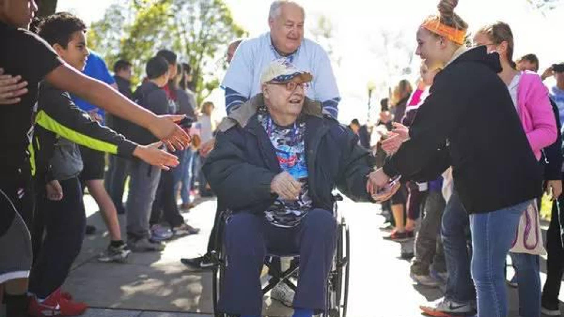 Anthony Petruzzi, 92, a veteran of World War II, Korea, and Vietnam is greeted as he arrives with an Honor Fight group from Kansas City, Mo., at the WWII Memorial on Veteran's Day, November 11.