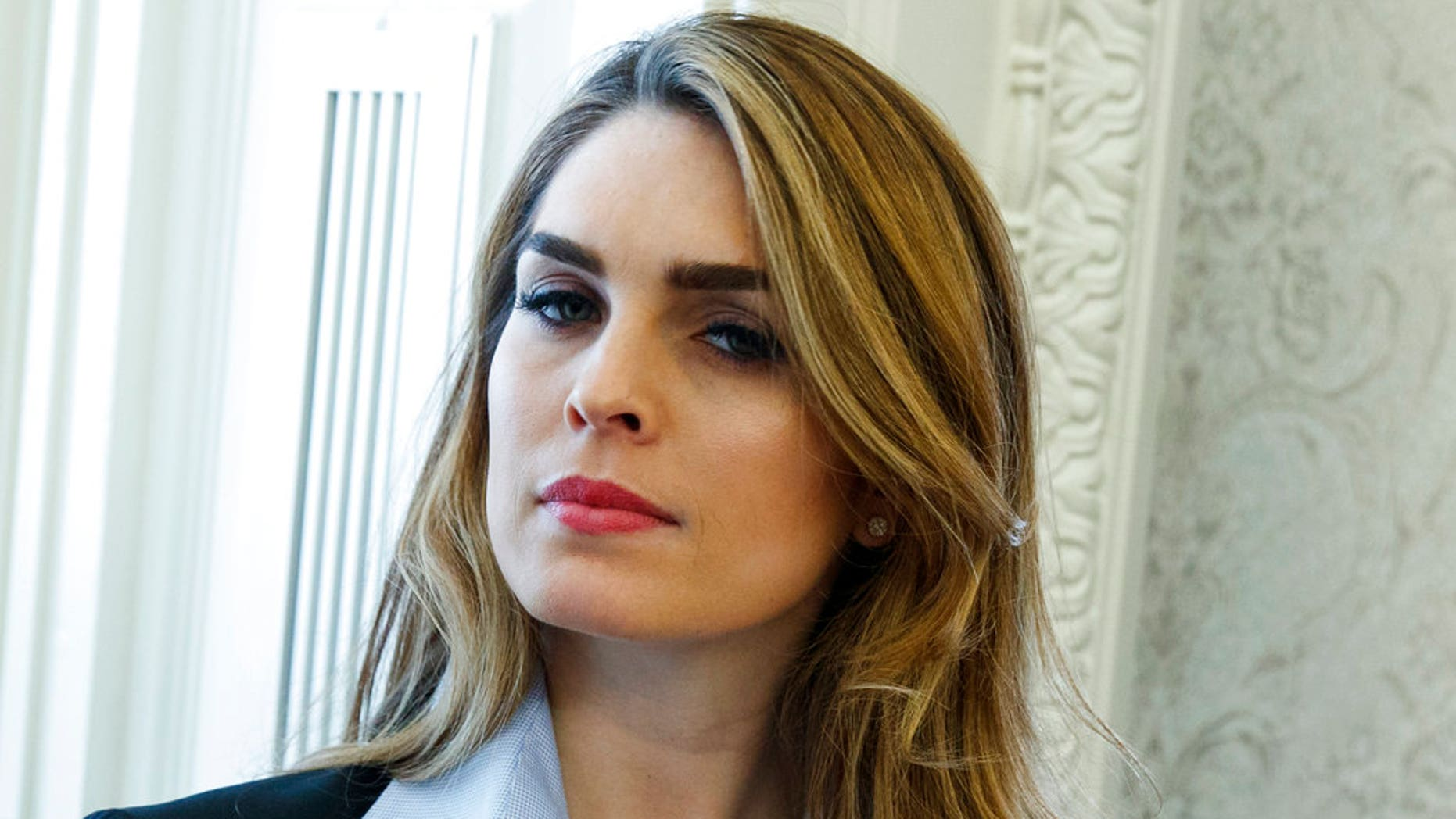 """In this Feb. 9, 2018 photo, White House Communications Director Hope Hicks is shown during a meeting in the Oval Office between President Donald Trump and Shane Bouvet, in Washington.  Hicks, one of President Donald Trump's most loyal aides, is resigning. In a statement, the president praises Hicks for her work over the last three years. He says he """"will miss having her by my side."""" The news comes a day after Hicks was interviewed for nine hours by the panel investigating Russia interference in the 2016 election and contact between Trump's campaign and Russia.  (AP Photo/Evan Vucci)"""