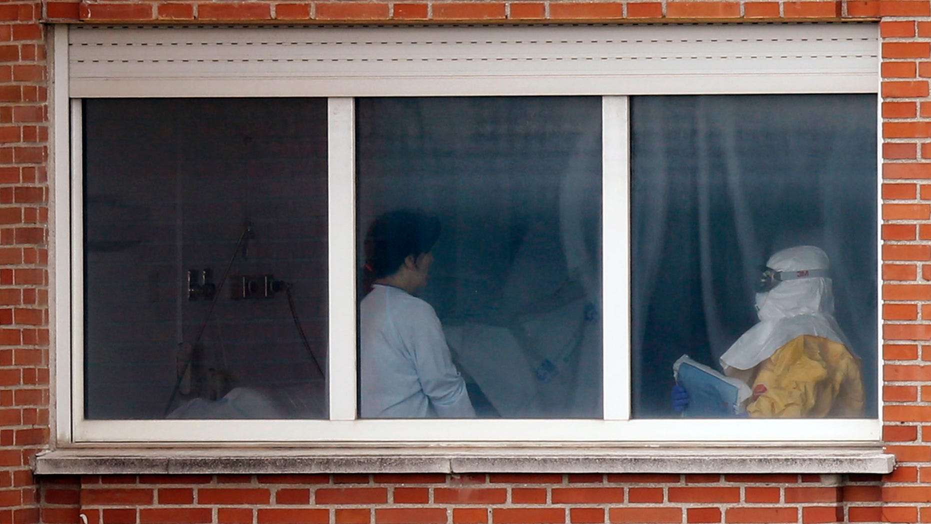 Oct. 9, 2014: A medical practitioner wearing protective clothing, right, stands next to an isolated patient on the sixth floor of the the Carlos III hospital in Madrid, Spain.