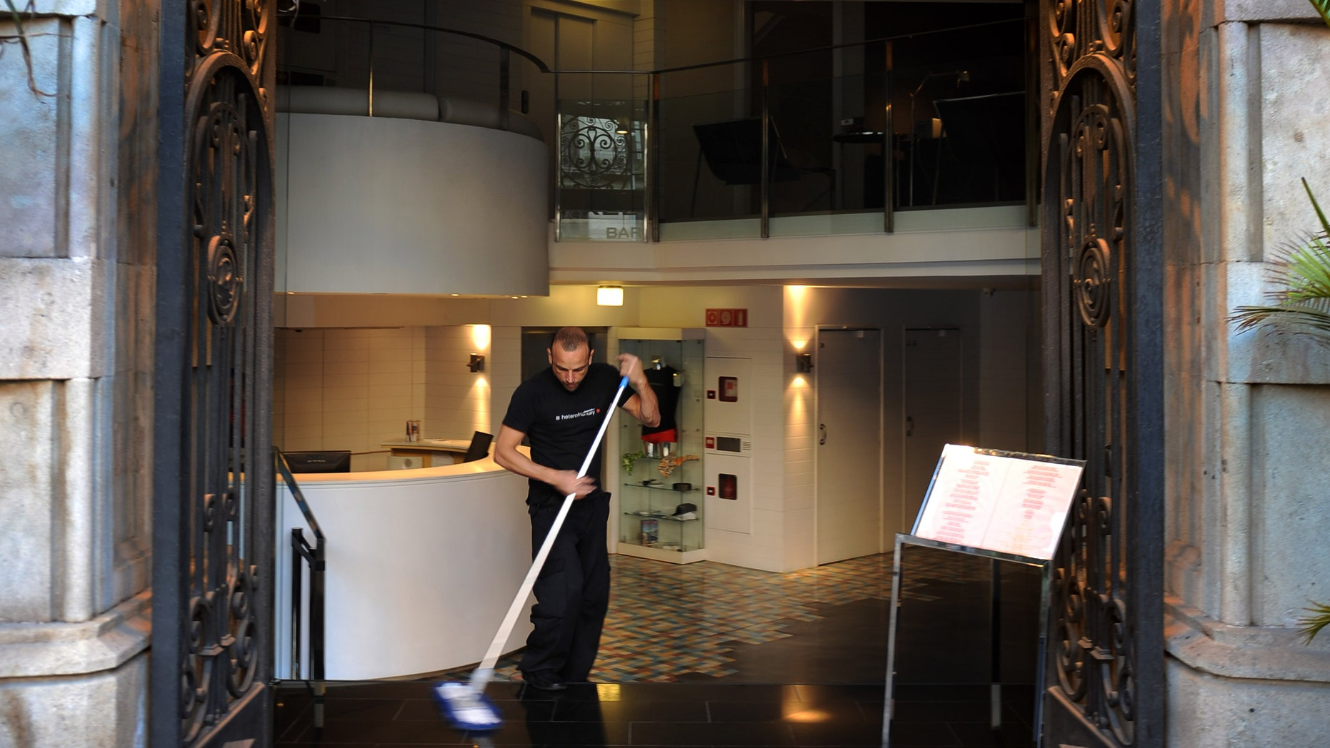 BARCELONA, SPAIN - MARCH 17:  A worker cleans the entrance of the Axel Hotel on March 17, 2009 in Barcelona, Spain. Axel Hotel is the first international hotel chain to cater specifically to homosexuals. Axel Hotels has also opened hotels in Berlin and Buenos Aires.  (Photo by Jasper Juinen/Getty Images)