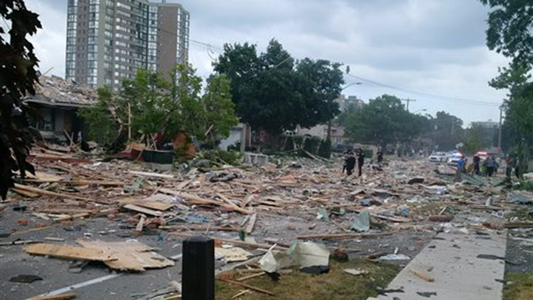 Debris litters a street after a house explosion in Mississauga, Ontario, Tuesday, June 28, 2016.