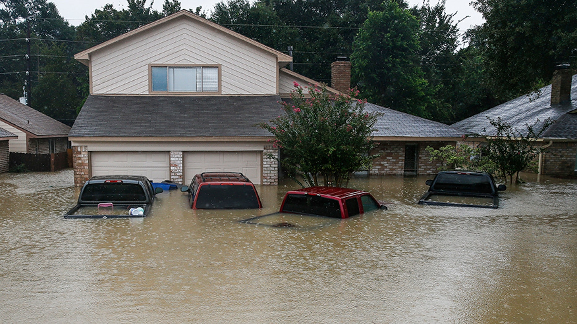 FILE - In this Aug. 29, 2017, file photo, trucks are submerged on Pine Cliff Drive in Houston during heavy rainfall from Tropical Storm Harvey. Few American cities depend on cars as much as Houston, and Harvey's record rainfall left flooded roads and neighborhoods with cars submerged and, in most cases, impossible to salvage. (Michael Ciaglo/Houston Chronicle via AP)