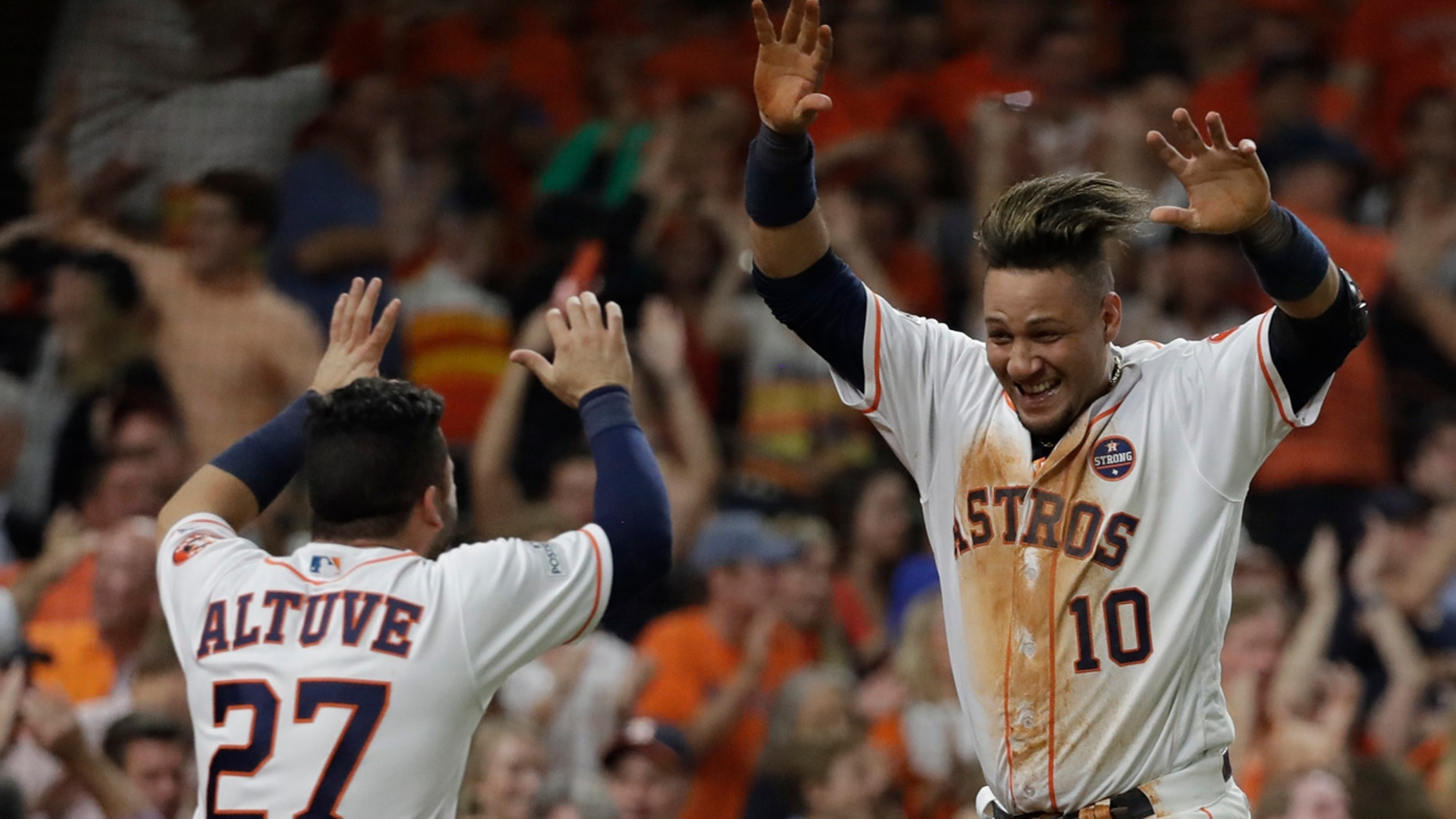 Houston Astros' Yuli Gurriel is congratulated by Jose Altuve after scoring during the fifth inning of Game 7 of baseball's American League Championship Series against the New York Yankees Saturday, Oct. 21, 2017, in Houston.