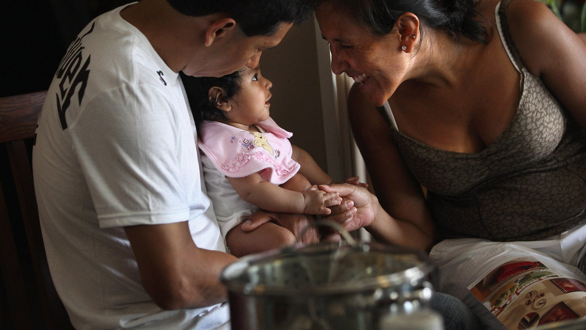 DENVER, CO - JULY 10:  Undocumented Mexican immigrant Jeanette Vizguerra sits with her husband Salvador and daughter Zuri, 5 months, on July 10, 2011 in Denver, Colorado. Vizguerra, a mother of four children, three of whom were born in the U.S. as American citizens, is facing a deportation hearing July 13 at Denver's Federal Courthouse. If Vizguerra is deported back to Mexico, she says her husband and children will stay on in the United States. Just one of millions of undocumented immigrants living in the U.S., Vizguerra first came to Colorado from Mexico City with her husband and first child 14 years before. Now an activist for the immigration advocate group Rights For All People, she also owns a janitorial service and says she has always paid state and federal taxes on her income. Some two years ago she was stopped by a traffic policemen for driving with expired tags and taken to jail when she could not prove her legal immigration status. Out on bail during court proceedings, she now faces the real possibility that she will be deported to Mexico and separated from her family in the United States.  (Photo by John Moore/Getty Images)