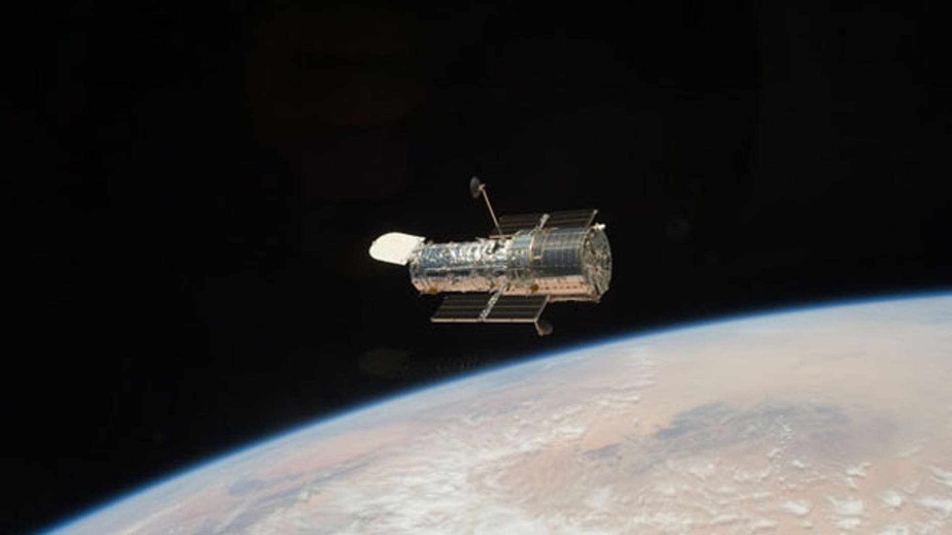 The Hubble Space Telescope orbits high above the Earth, after it was released at the close of the STS-125 servicing mission.