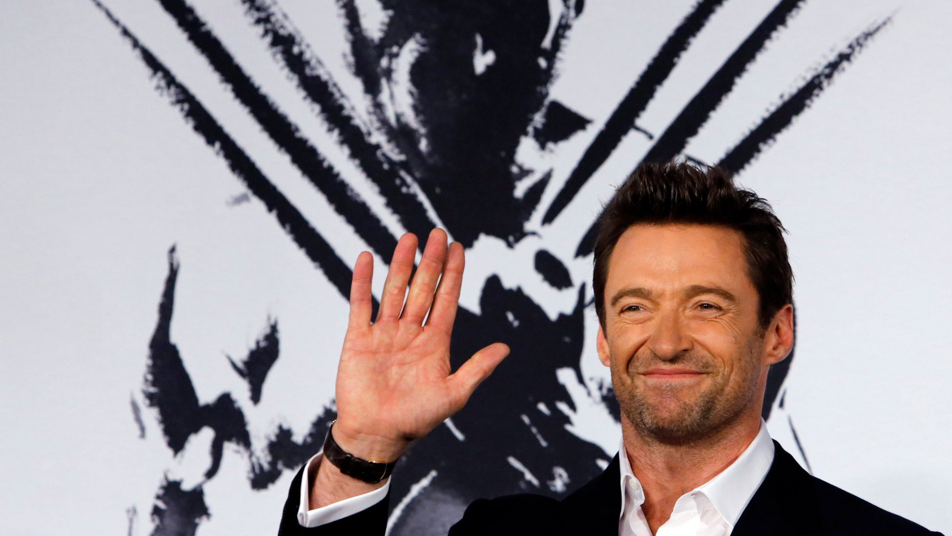 """August 28, 2013. Hugh Jackman waves to fans as he attends the Japan premiere of his movie """"The Wolverine"""" in Tokyo."""