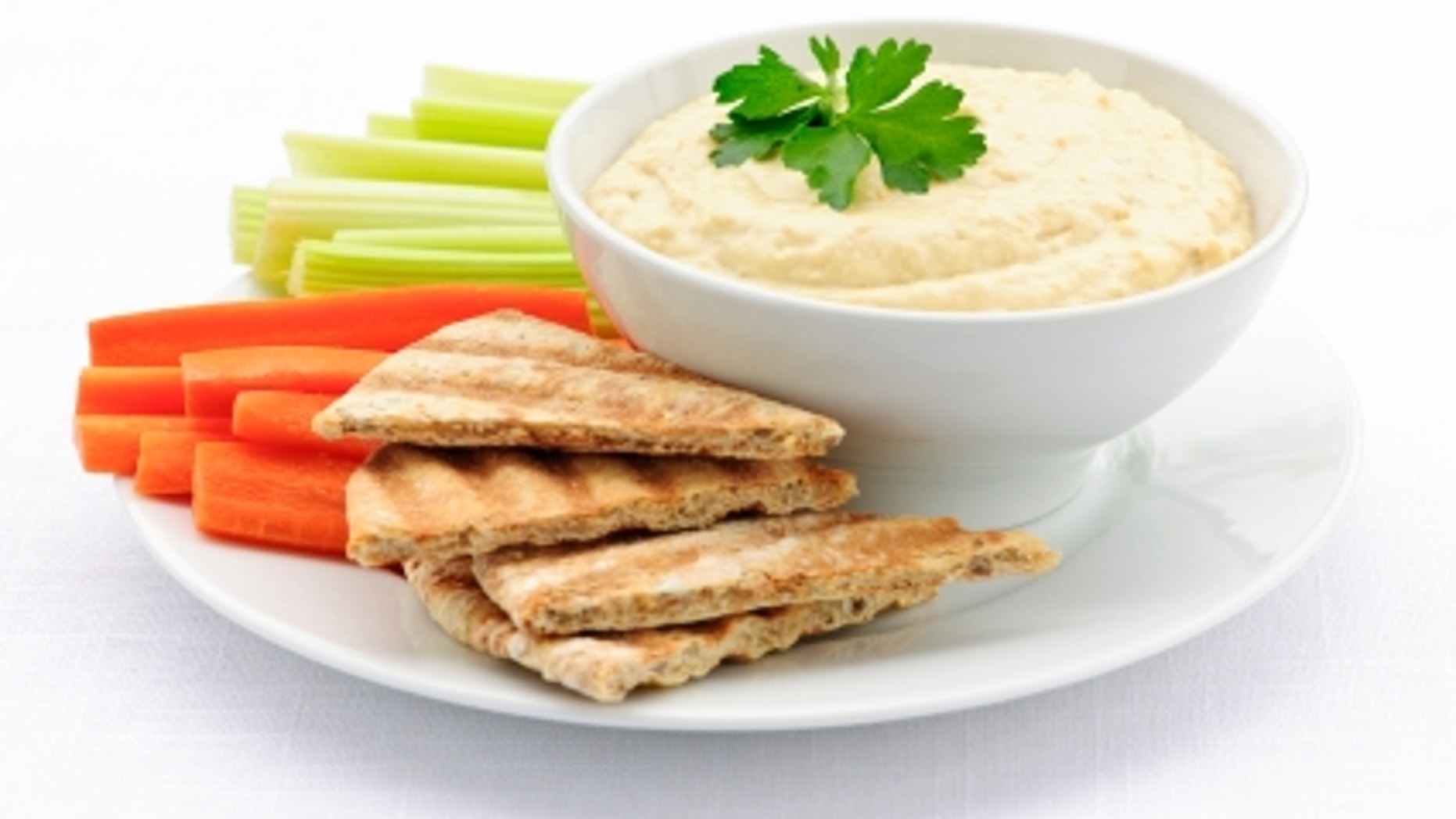 Healthy snack of hummus dip with pita bread slices and vegetables