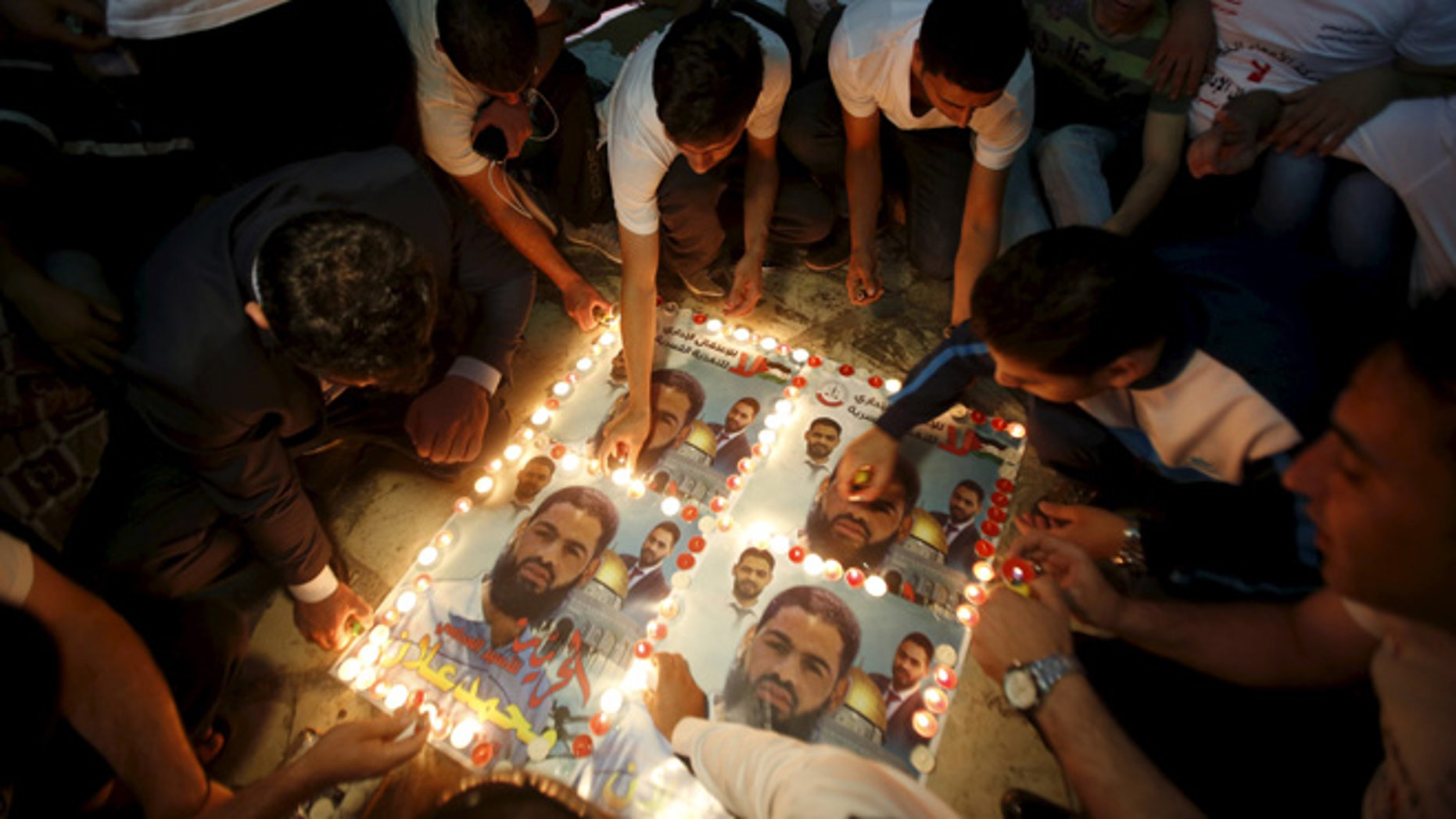 Aug. 19: Palestinians light candles on posters depicting Palestinian detainee Mohammed Allan during a protest in support of Allan in the West Bank city of Hebron.