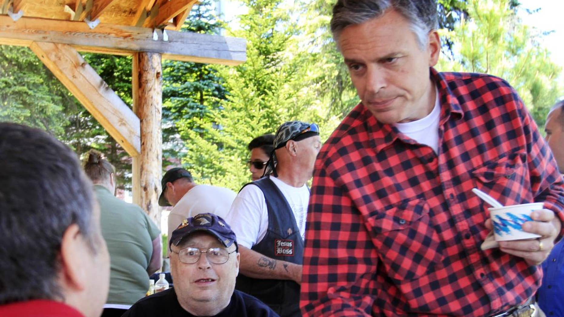 With his wife Mary Kaye at his side possible 2012 presidential hopeful, former Republican Gov. Jon Huntsman, Jr., of Utah shakes hands during a cultural festival at Heritage Park, Saturday, June 4, 2011 in Berlin, N.H. (AP Photo/Jim Cole)