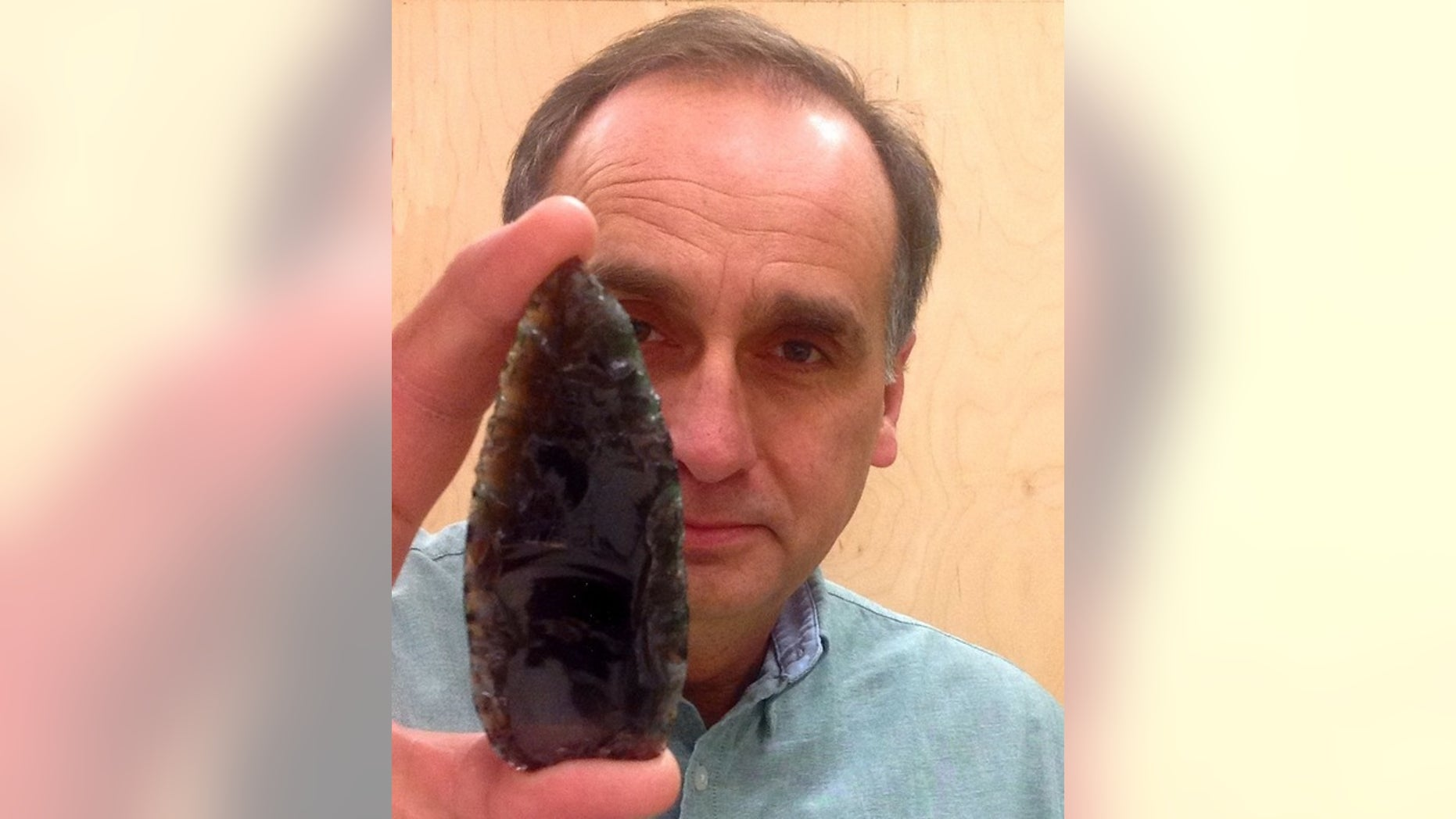 Karl Hutchings, an archaeologist at Thompson Rivers University in Canada, holds a Clovis spear point.