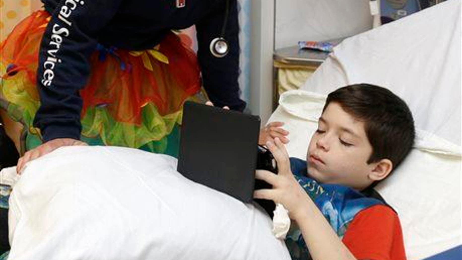 Registered nurse Nicole Maggi talks to patient Leonardo Salazar, seven-years-old, as he plays with his iPad mini ON Tutu Tuesday at Joe DiMaggio Children���s Hospital in Hollywood, Fla., Tuesday, March 24, 2015.