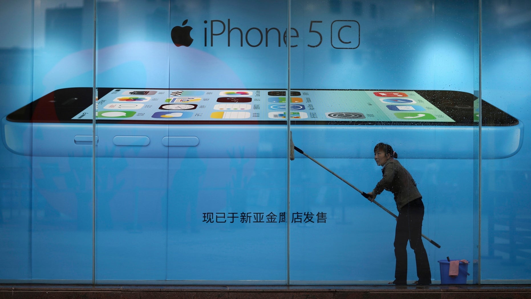 A worker cleans glass in front of an iPhone 5C advertisement at an apple store in Kunming, Yunnan province, in this October 27, 2013 file picture.