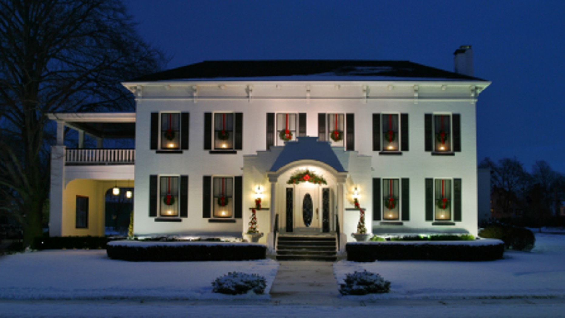 Holiday House. White house at dusk with candles wreaths in the windows.  Classicized Italianate architecture with painted brick facade.