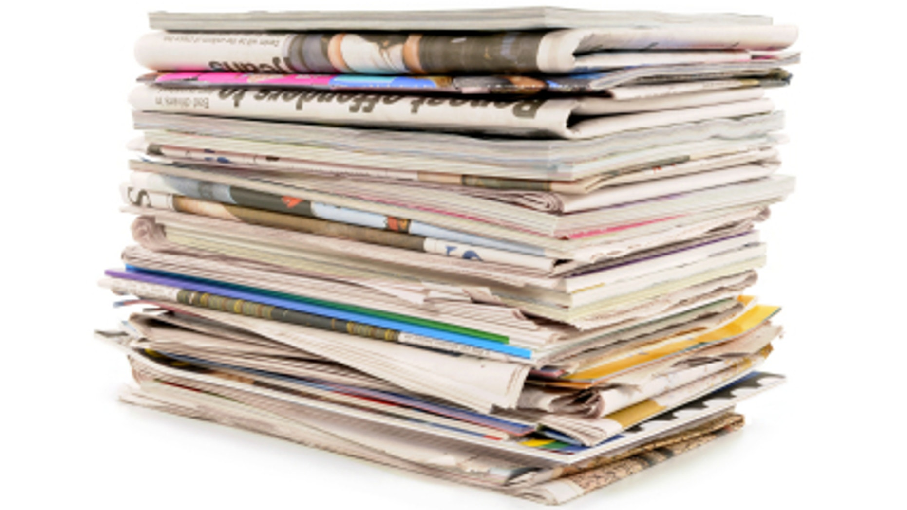 Pile of old newspapers and magazines against a white background