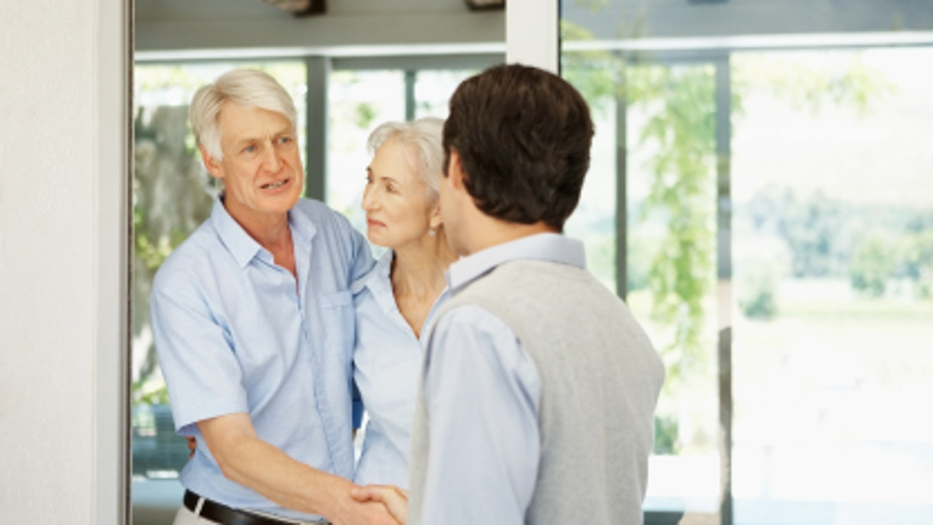 Successful elderly couple welcoming a guest at their house