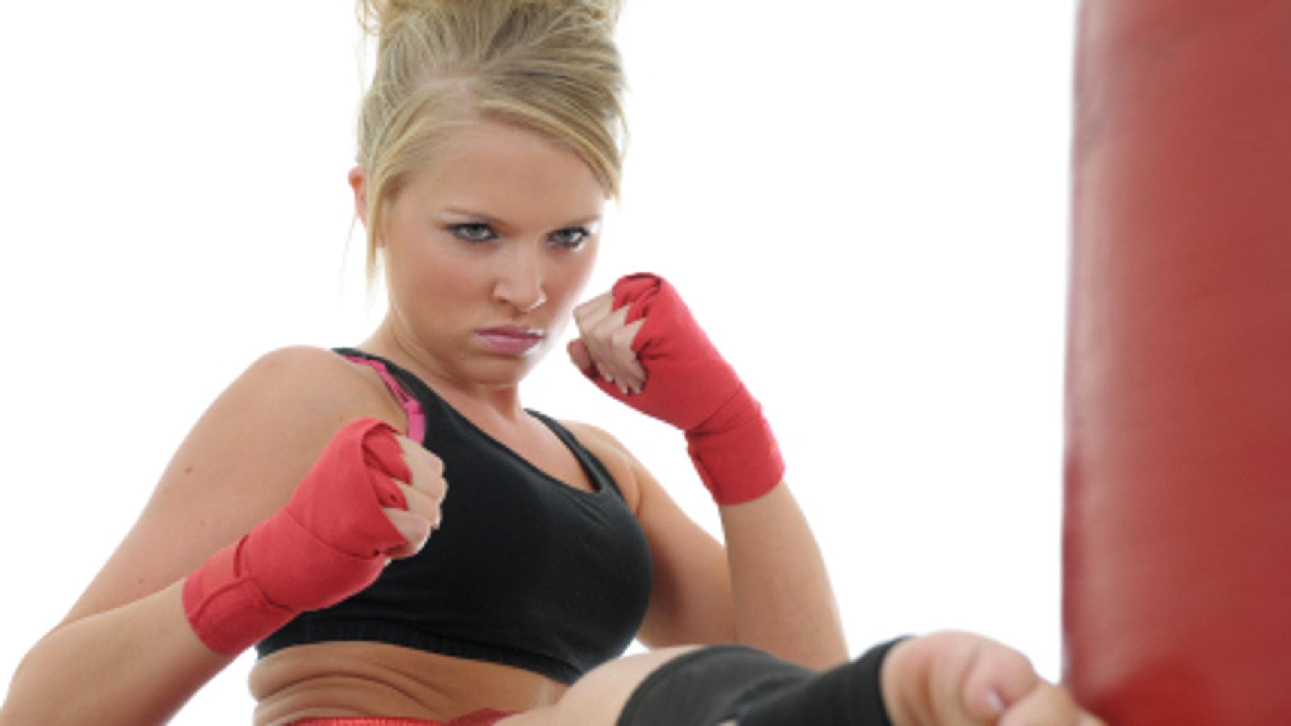 Kickboxer kicking a heavy bag.