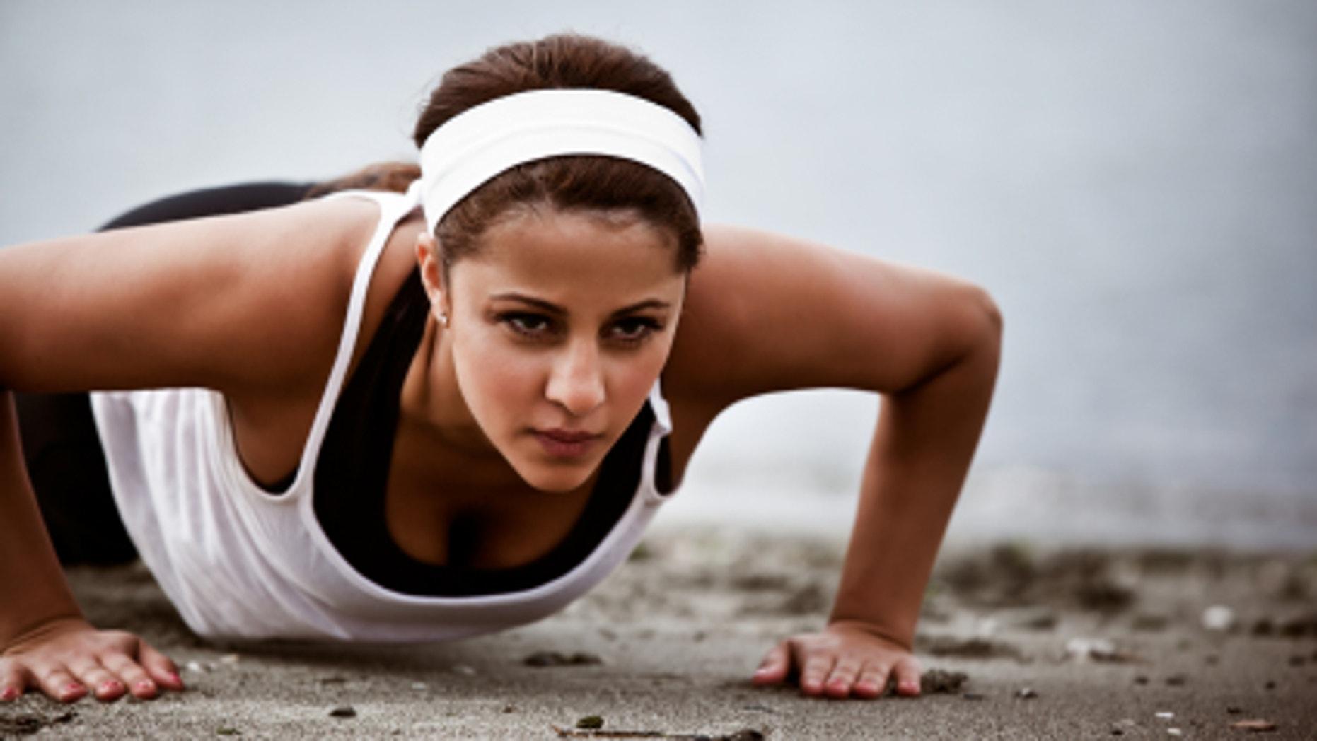 A beautiful asian woman doing push up at a beach
