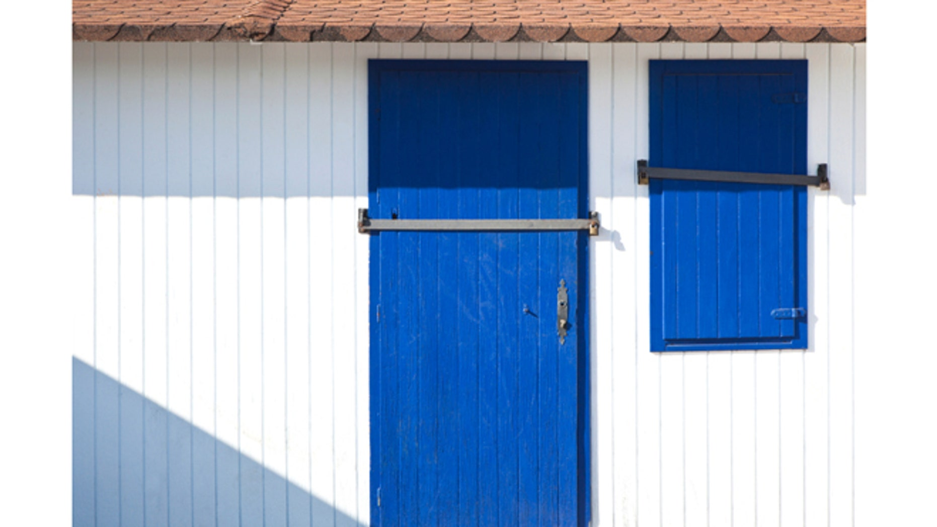 Blue door and window of a closed beach hut.
