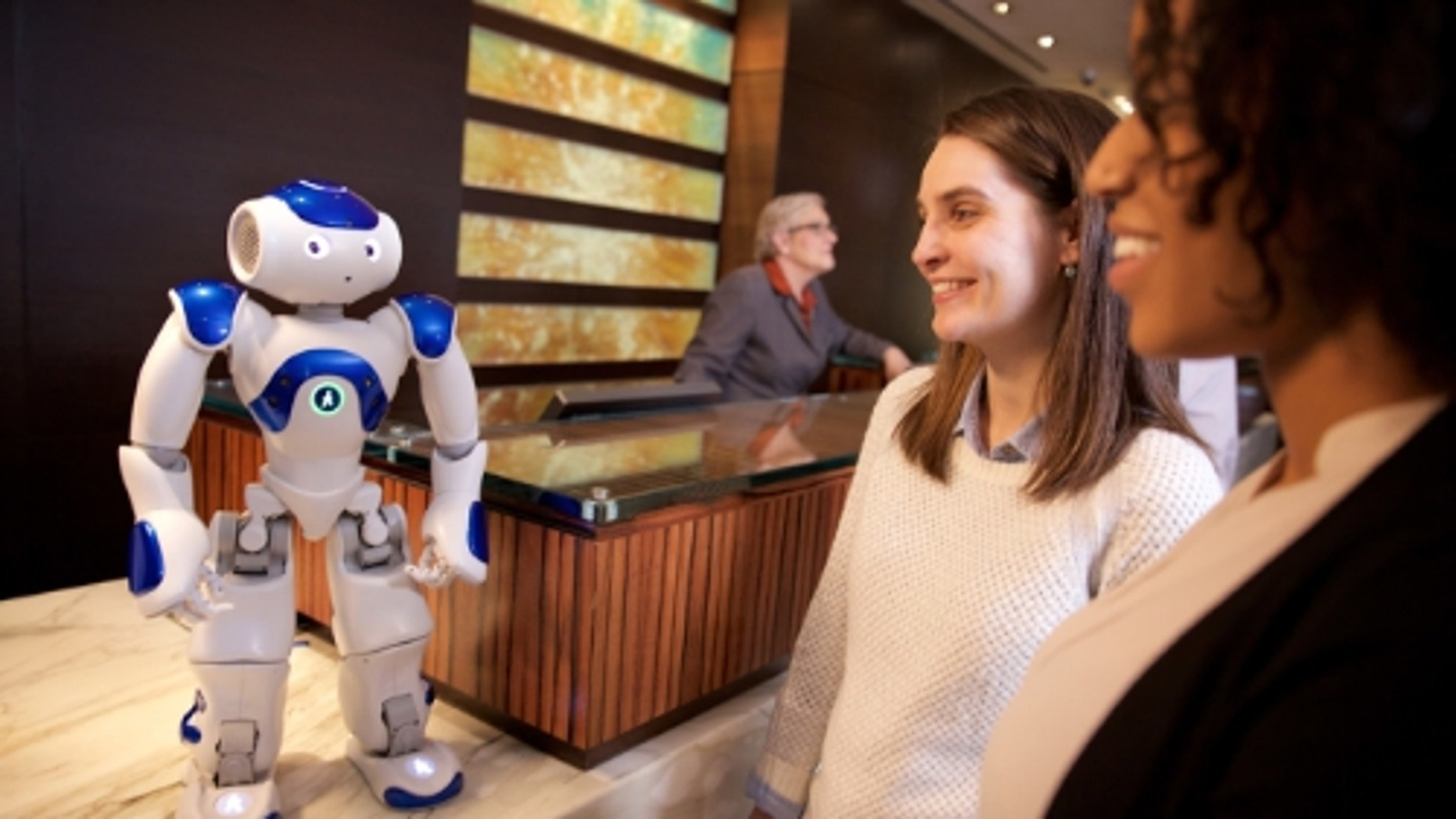 """Visitors to the Hilton Hotel in McLean, Va. meet """"Connie,"""" a robot concierge named after Conrad Hilton and powered by IBM Watson and WayBlazer. (Photo courtesy of Green Buzz Agency/Feature Photo Service for IBM) (PRNewsFoto/IBM)"""