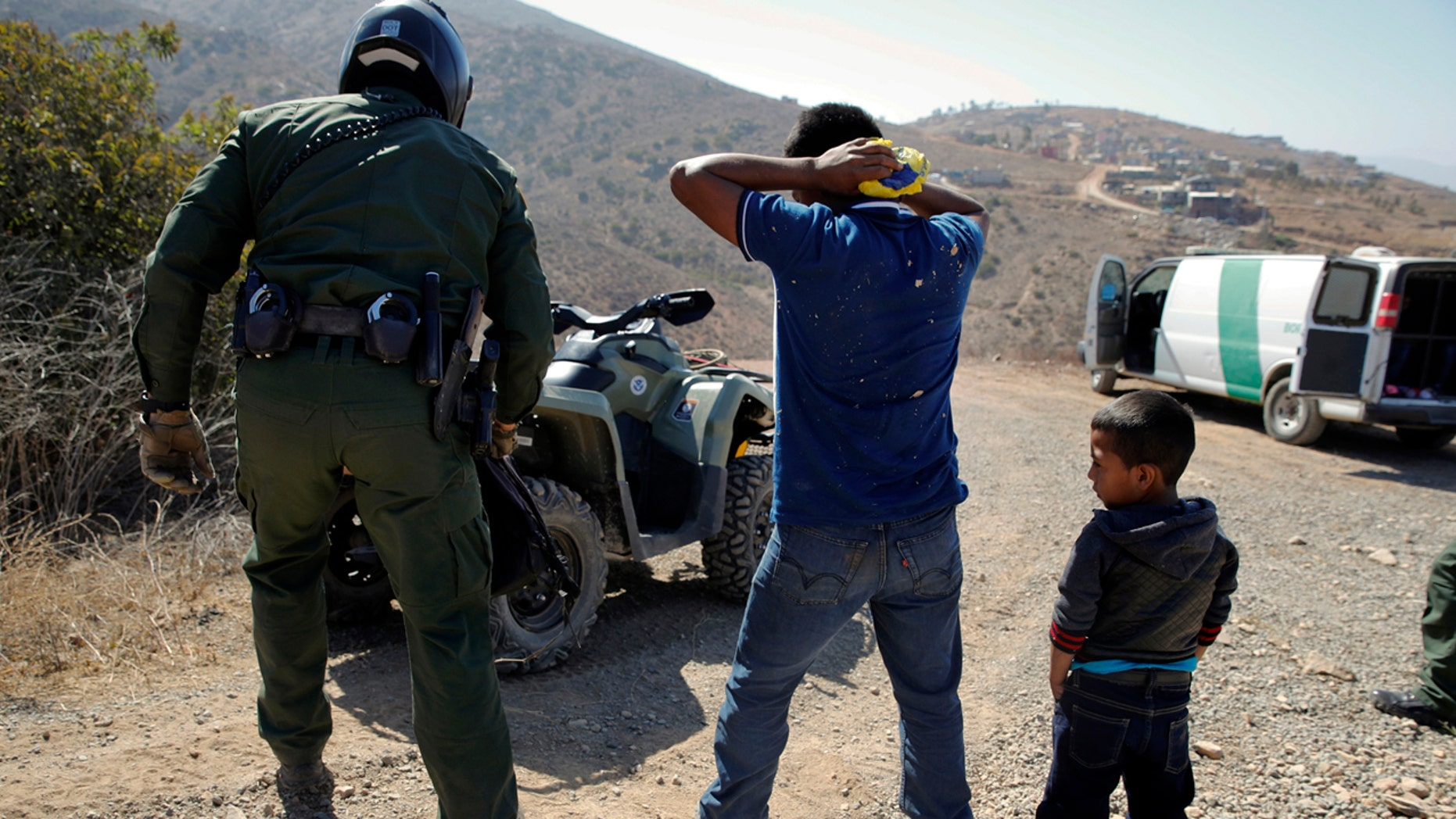 FILE - In this June 28, 2018, file photo, a Guatemalan father and son, who crossed the U.S.-Mexico border illegally, are apprehended by a U.S. Border Patrol agent in San Diego. California will introduce group trials on Monday, July 9, for people charged with entering the country illegally. Federal prosecutors in Arizona, Texas and New Mexico have long embraced these hearings, which critics call assembly-line justice. California was a lone holdout and the Justice Department didn't seriously challenge its position until the arrival of Attorney General Jeff Sessions. (AP Photo/Jae C. Hong, File)