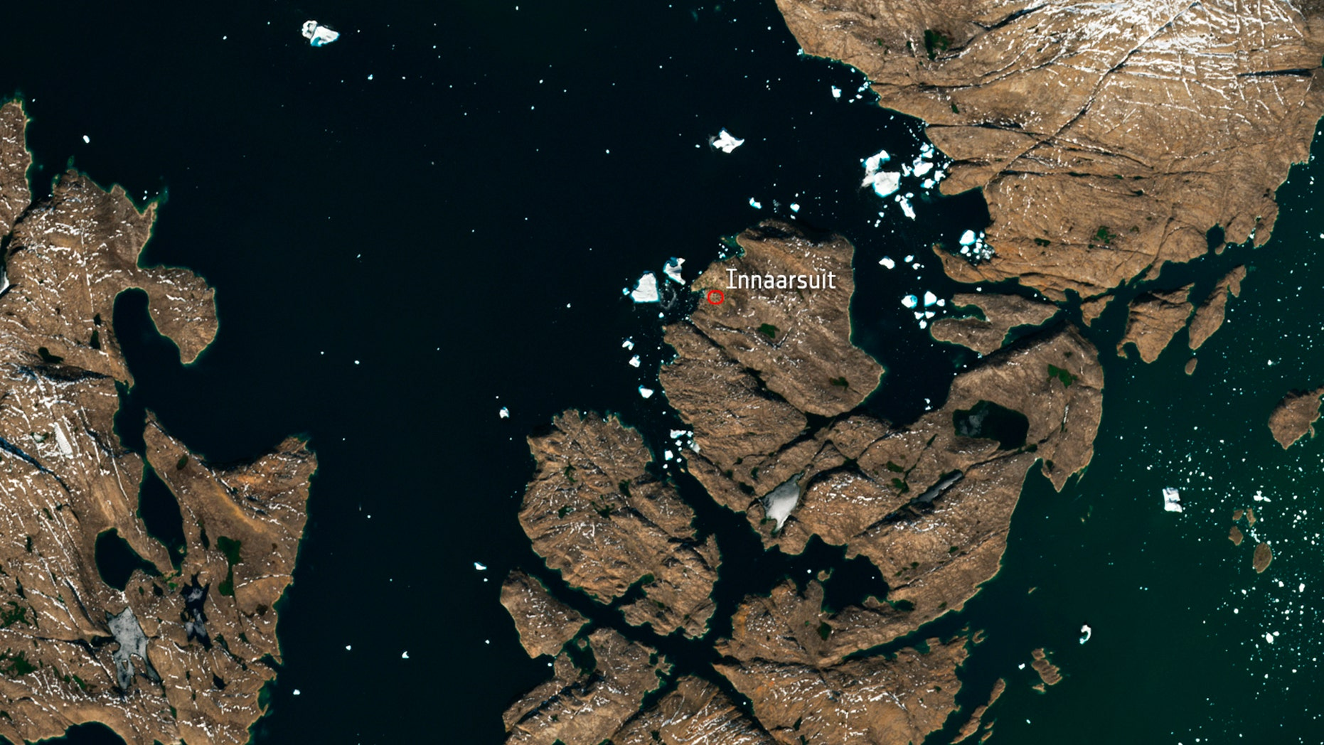 The satellite image, which was captured by Sentinel-2A on July 9, 2018, provided by European Space Agency esa on Tuesday, July 18, 2018 shows a huge iceberg perilously close to the village of Innaarsuit on the west coast of Greenland. If the berg breaks apart, waves resulting from the falling ice could wash away parts of the village. (esa via AP)