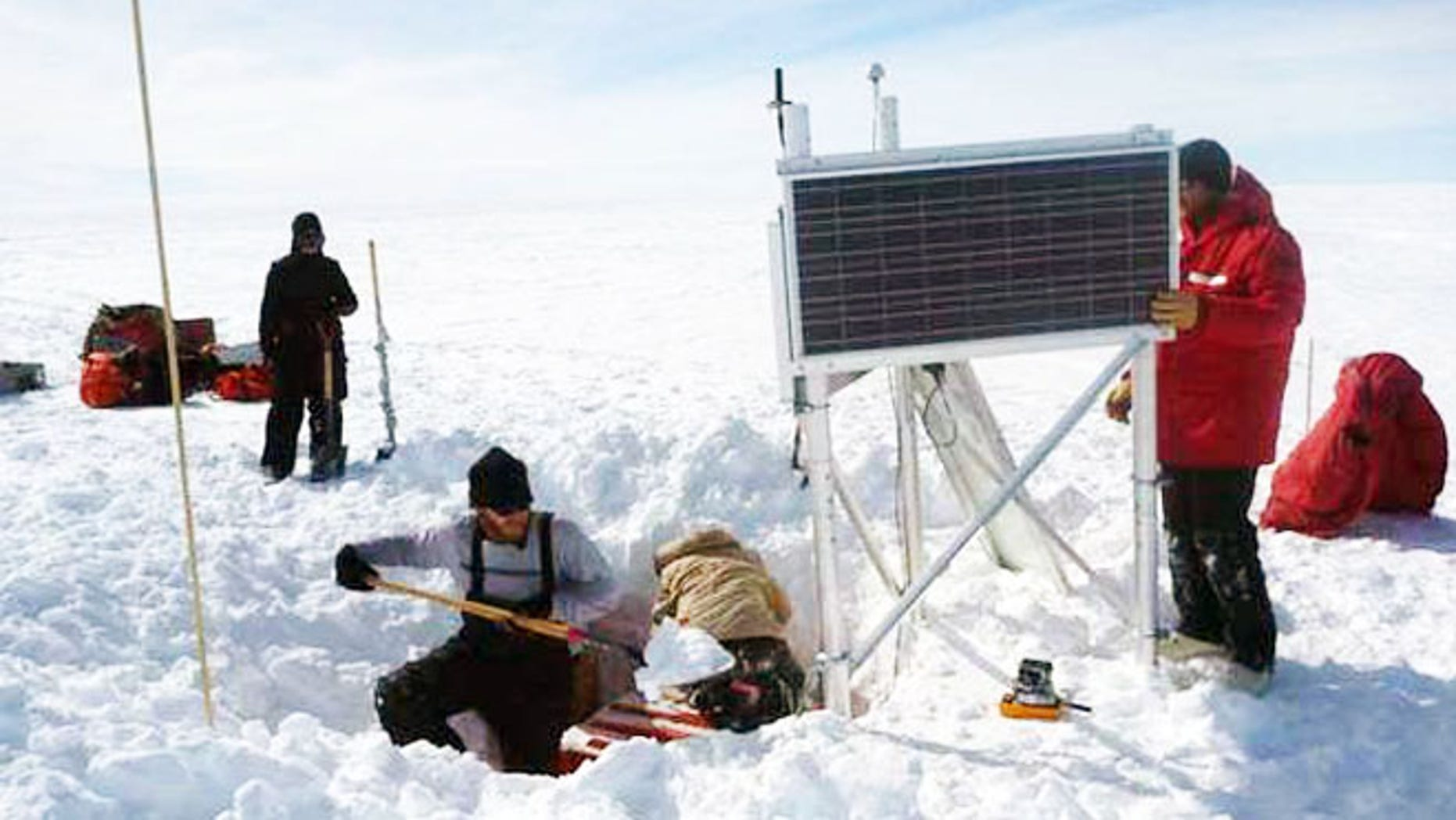 Researchers hard at work around a seismograph, an instrument in the orange box buried in a hole in the snow. Solar power runs the seismic station during the summer, and batteries keep it going during the long, dark winter months.