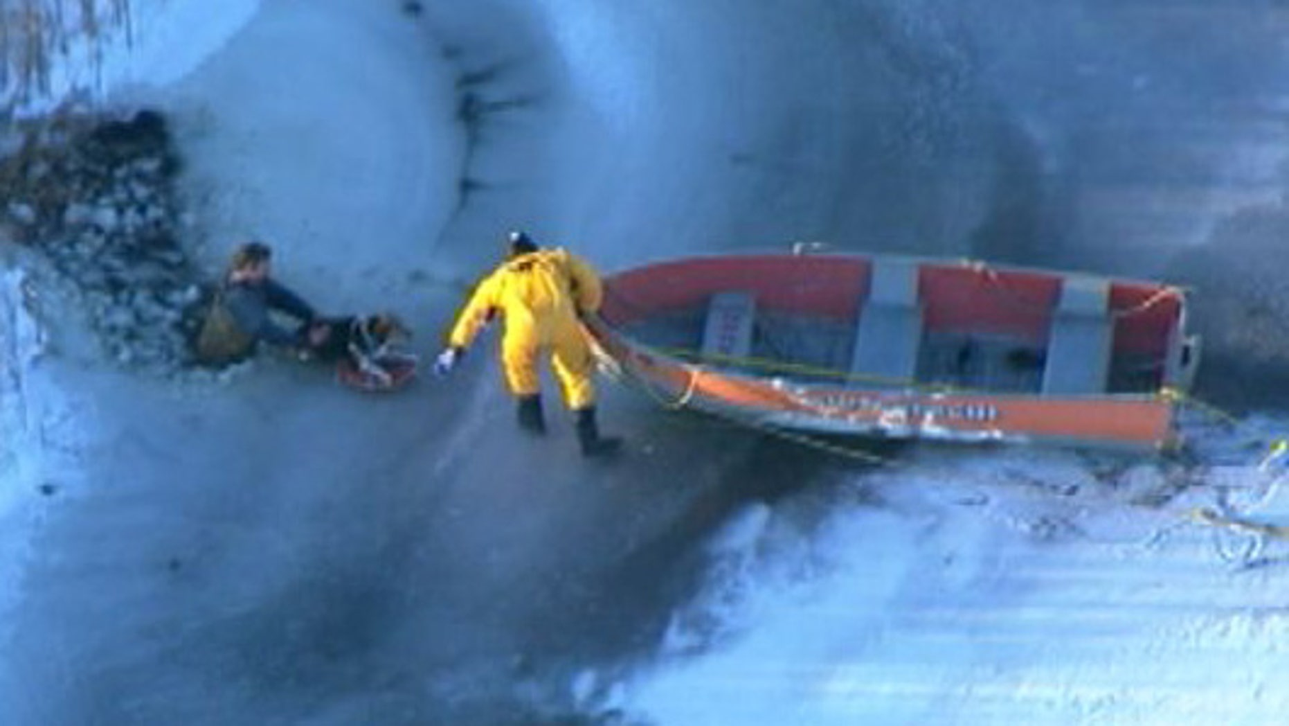 This image shows rescue workers pulling a Michigan man and a dog from frigid waters after the ice broke.
