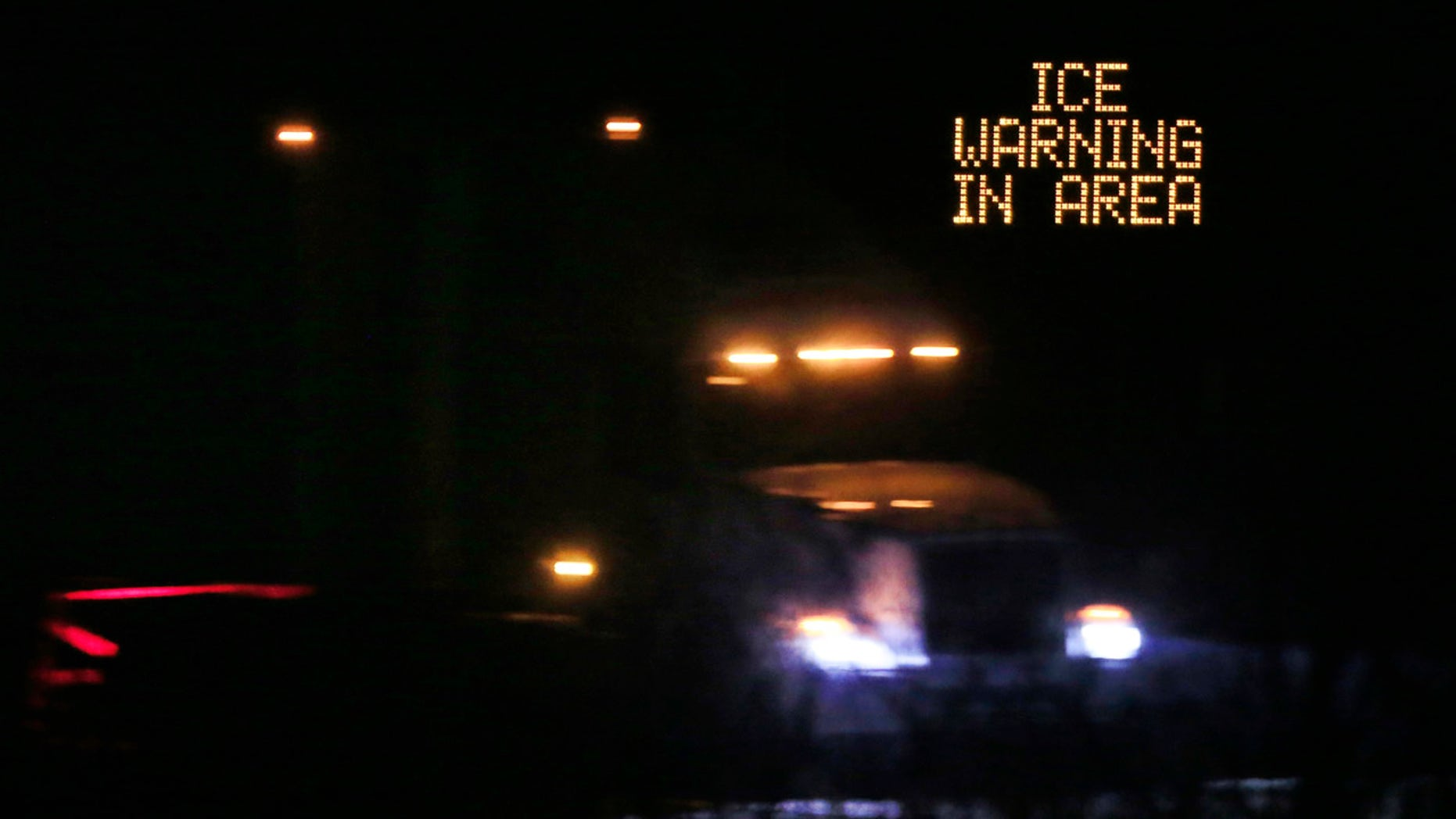 Jan. 14, 2017: Traffic moves past an icing warning sign at night on I-70 west of Lawrence, Kan.