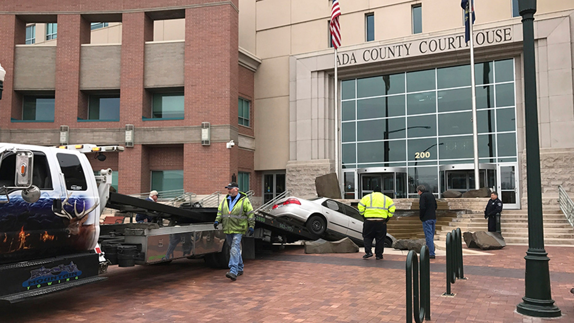 "Rescue crews remove a vehicle crashed earlier intentionally into the Ada County Courthouse fountain in Boise, Idaho, Sunday, Dec. 10, 2017. Authorities say Jonathan Locksmith upset with the court system tried to crash a car into the courthouse in the state's capital city Sunday morning, spinning his vehicle around in a ""doughnut"" before landing it in the fountain downtown Boise. Locksmith was arrested on a misdemeanor reckless driving charge and is now in jail. (Katy Moeller/The Idaho Statesman via AP)"