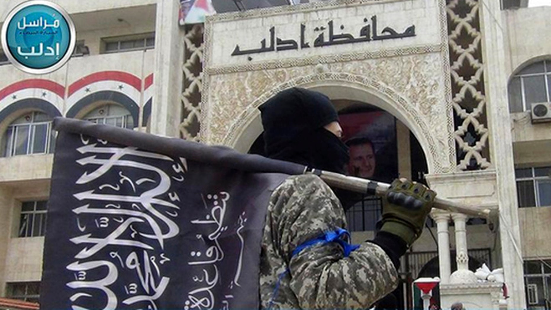 In this image posted on the Twitter page of Syria's al-Qaida-linked Nusra Front on Saturday, March 28, 2015, which is consistent with AP reporting, a fighter from Syria's al-Qaida-linked Nusra Front holds his group flag as he stands in front of the governor building in Idlib province, north Syria. (AP)