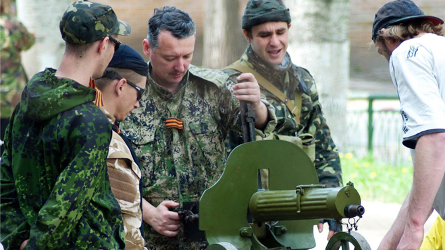 """April 23, 2014: Igor Strelkov, the defense minister of the self-proclaimed """"Donetsk People's Republic,"""" inspects a World War I-era machine gun looted from a local museum."""