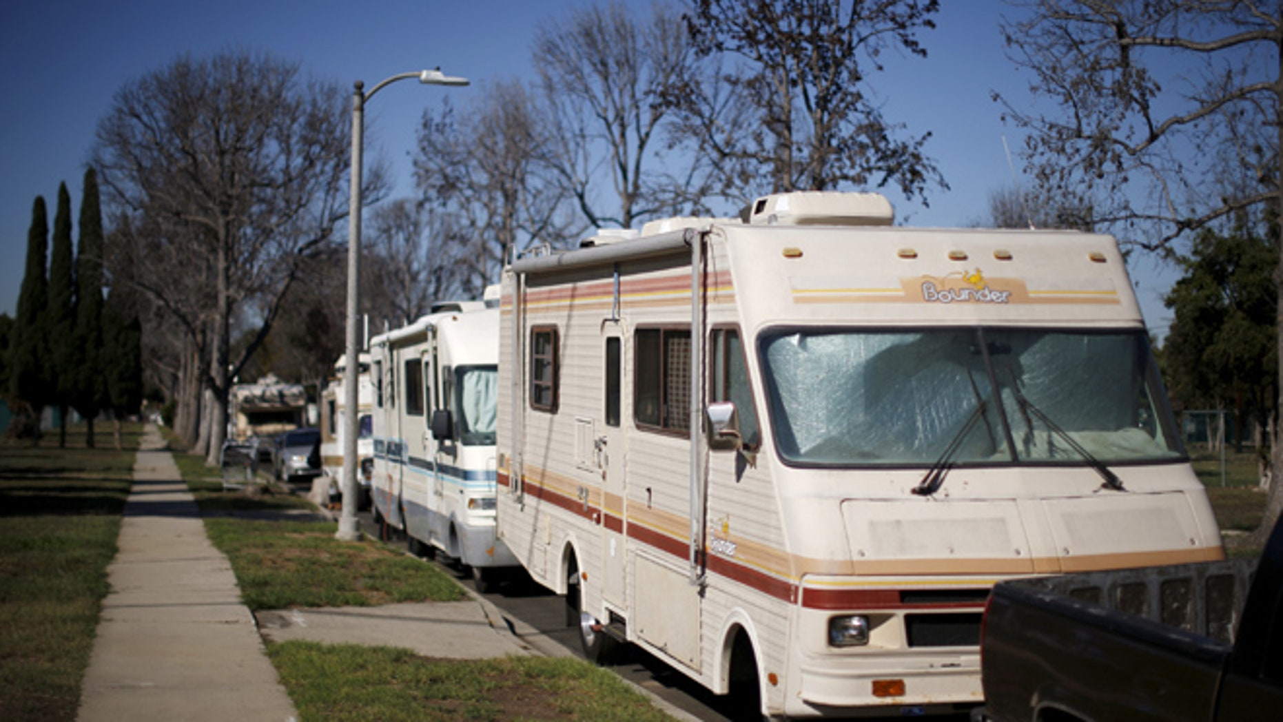 Motorhomes line the street in a homeless motorhome and tent encampment near LAX airport in Los Angeles, California, United States