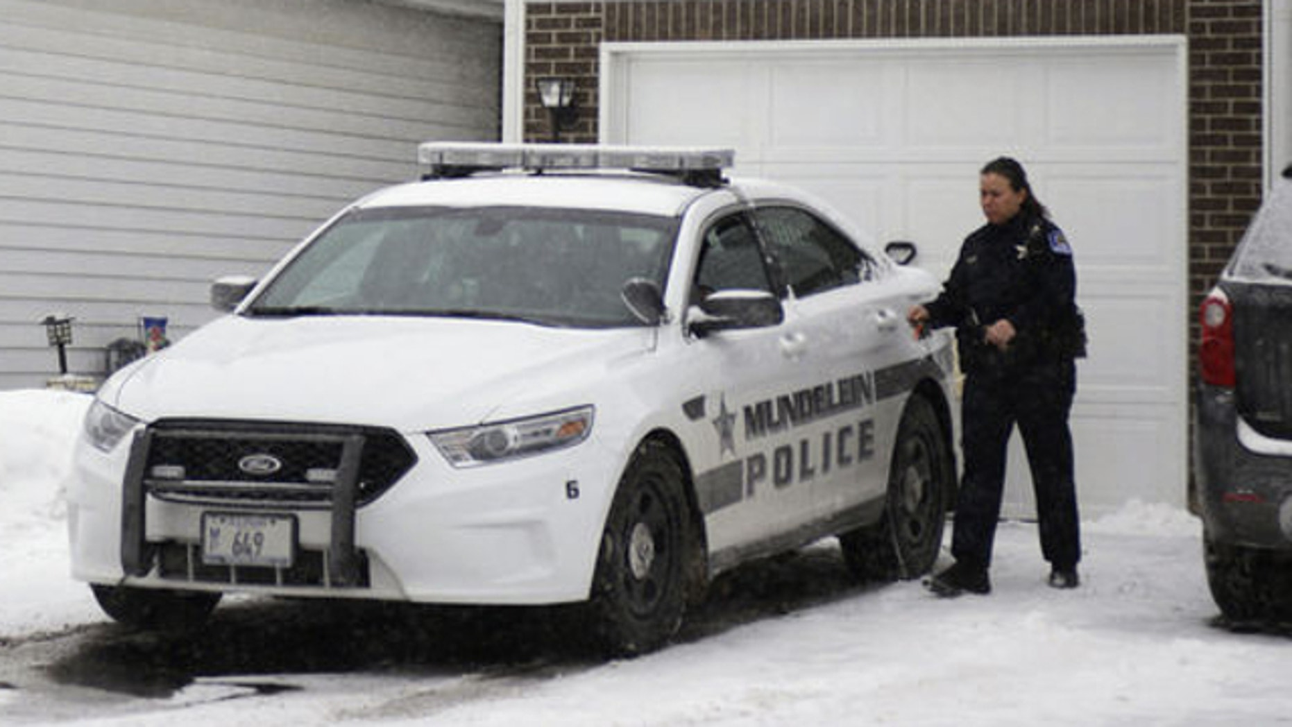 Jan. 22, 2014: A police officer is seen outside a home in Mundelein, Ill., where an 11-year-old girl was stabbed to death on Tuesday, Jan. 21. The Lake County State's Attorney's office said Wednesday they've approved a first-degree murder charge against a 14-year-old girl in the killing.